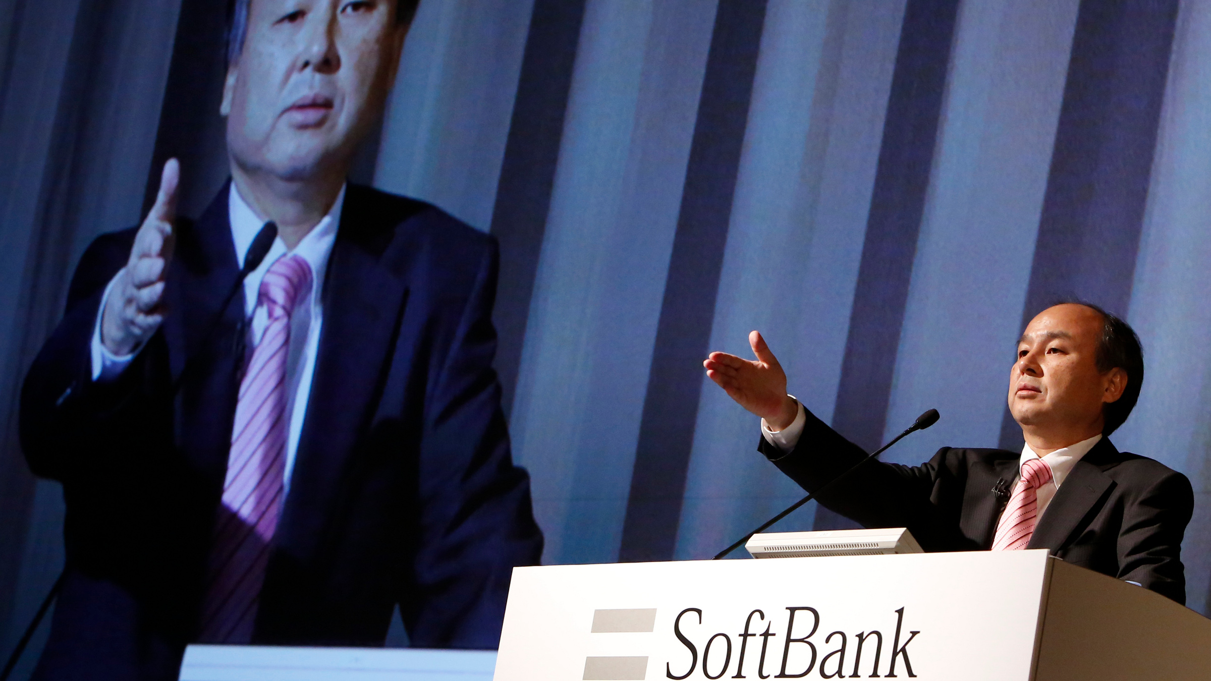 Softbank Corp CEO Masayoshi Son gestures towards a reporter during a news conference in Tokyo February 12, 2014. SoftBank Corp, which runs Japan's third-largest mobile carrier by subscriber numbers, reported a dip in third-quarter net profit after a string of acquisitions incurred steep integration costs.