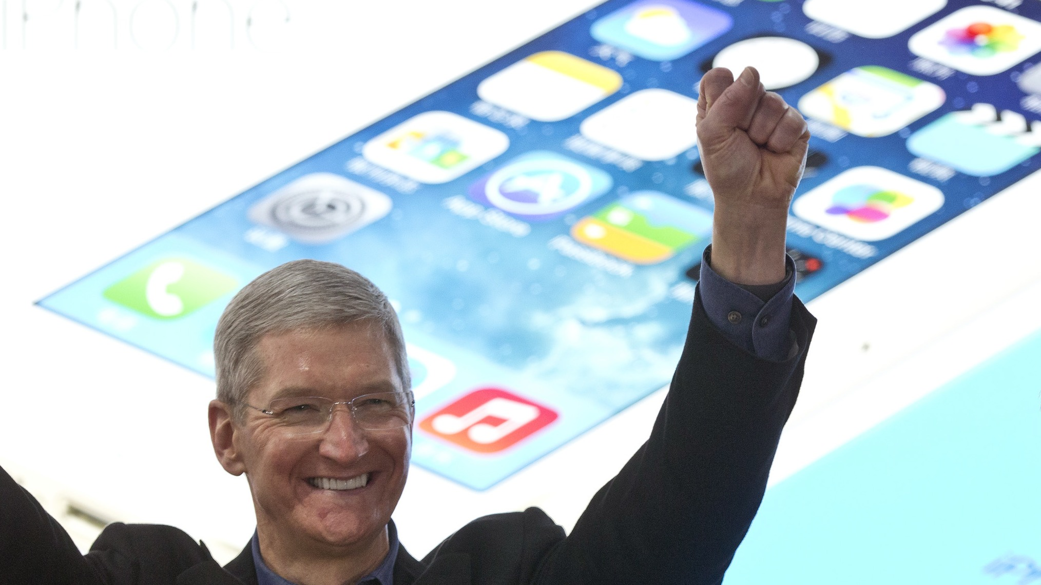 Apple's CEO Tim Cook, left, gestures with China Mobile's chairman Xi Guohua, right, during a promotional event that marks the opening day of sales of China Mobile's 4G iPhone 5s and iPhone 5c at a shop of the world's largest mobile phone operator in Beijing, China, Friday, Jan. 17, 2014. (AP Photo/Alexander F. Yuan)
