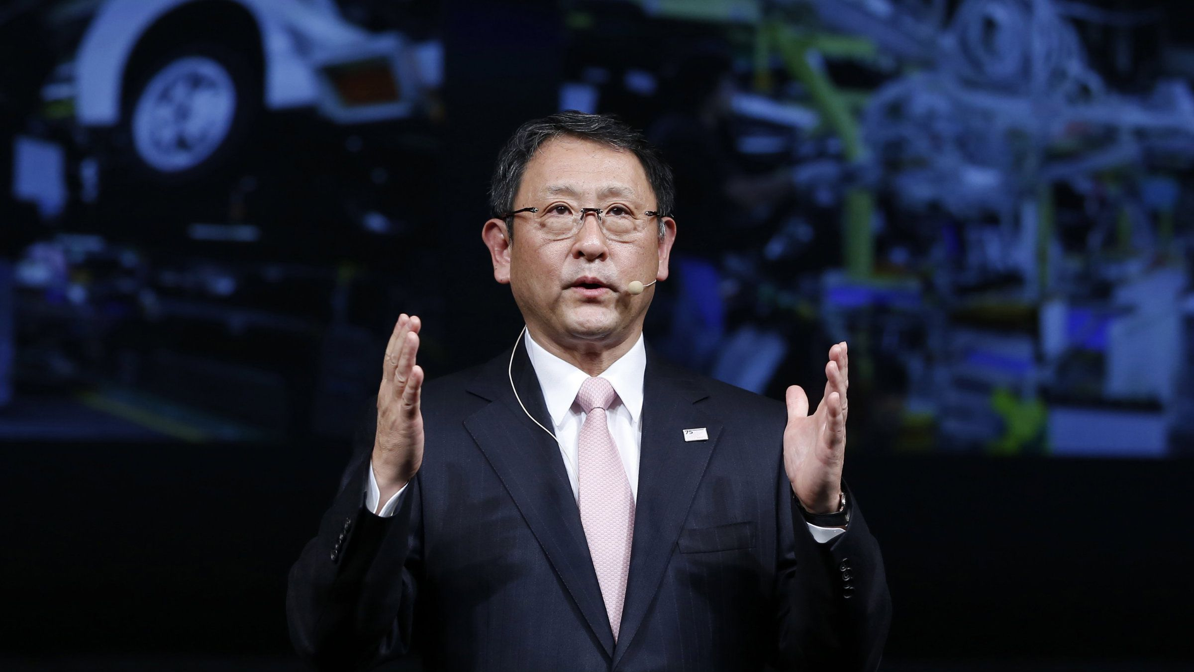 Toyota President Akio Toyoda attempts to show the approximate size of the wage increase.
