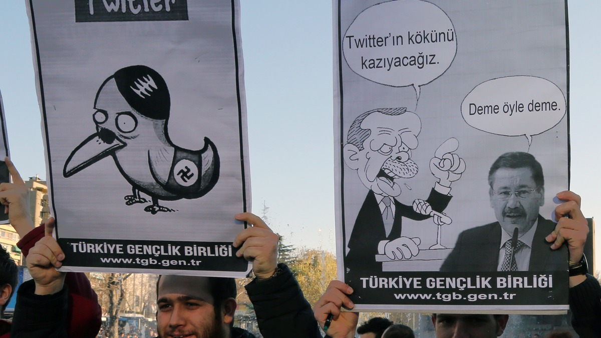 """Members of the Turkish Youth Union hold cartoons depicting Turkey's Prime Minister Recep Tayyip Erdogan during a protest against a ban on Twitter, in Ankara, Turkey, Friday, March 21, 2014. Turkey's attempt to block access to Twitter appeared to backfire on Friday with many tech-savvy users circumventing the ban and suspicions growing that the prime minister was using court orders to suppress corruption allegations against him and his government. Cartoon in center reads: Erdogan, left, to his Ankara Mayor Melih Gokcek """" we will rip out the roots of Twitter."""" Gokcek: """"don't say it.""""(AP Photo/Burhan Ozbilici)"""