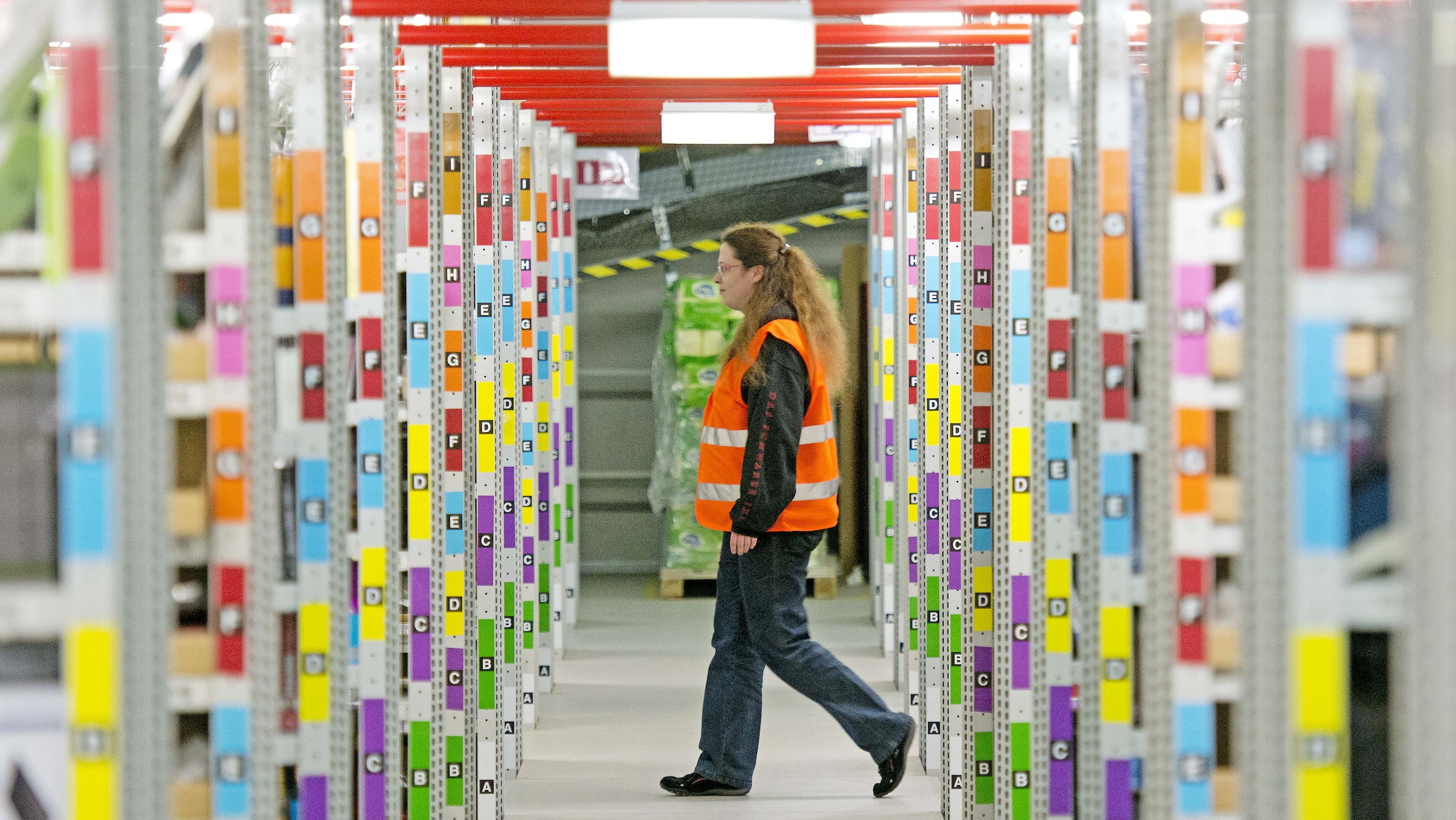 An employee walks in the distribution center of the online retailer Amazon in Leipzig, central Germany, Wednesday, March 26, 2014. (AP Photo/Jens Meyer)
