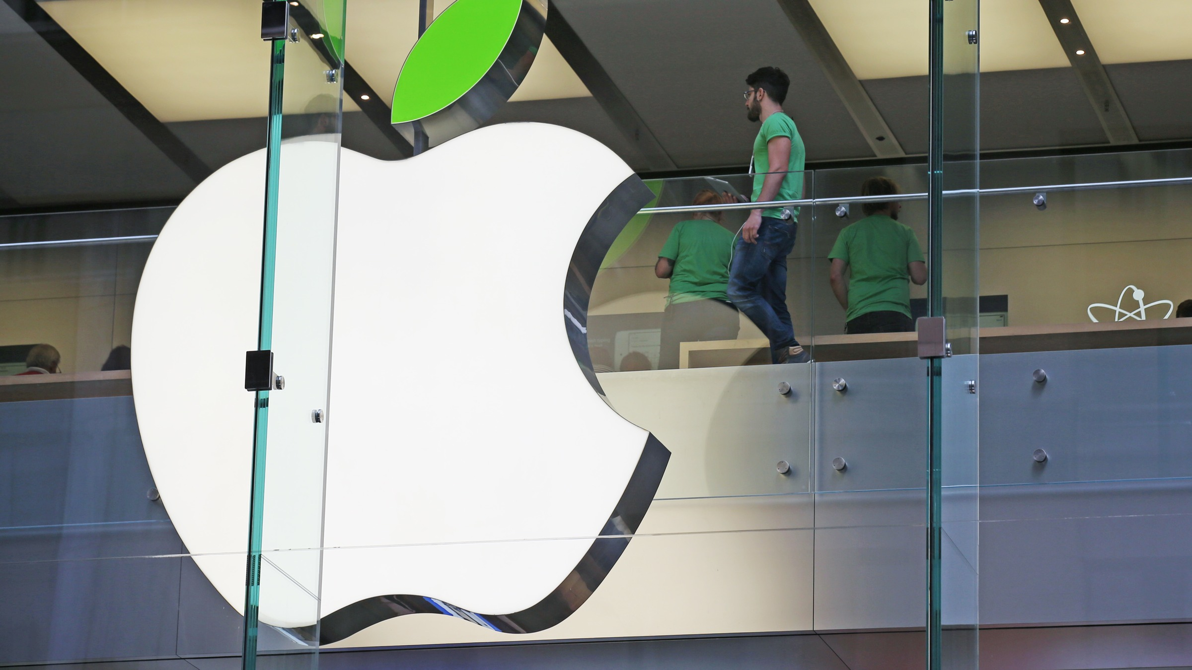 Employees wear green shirts near Apple's familiar logo displayed with a green leaf at the Apple Store timed to coincide with Tuesday's annual celebration of Earth Day in Sydney, Tuesday, April 22, 2014. Apple is offering free recycling of all its used products and vowing to power all of its stores, offices and data centers with renewable energy to reduce the pollution caused by its devices and online services. (AP Photo/Rick Rycroft)