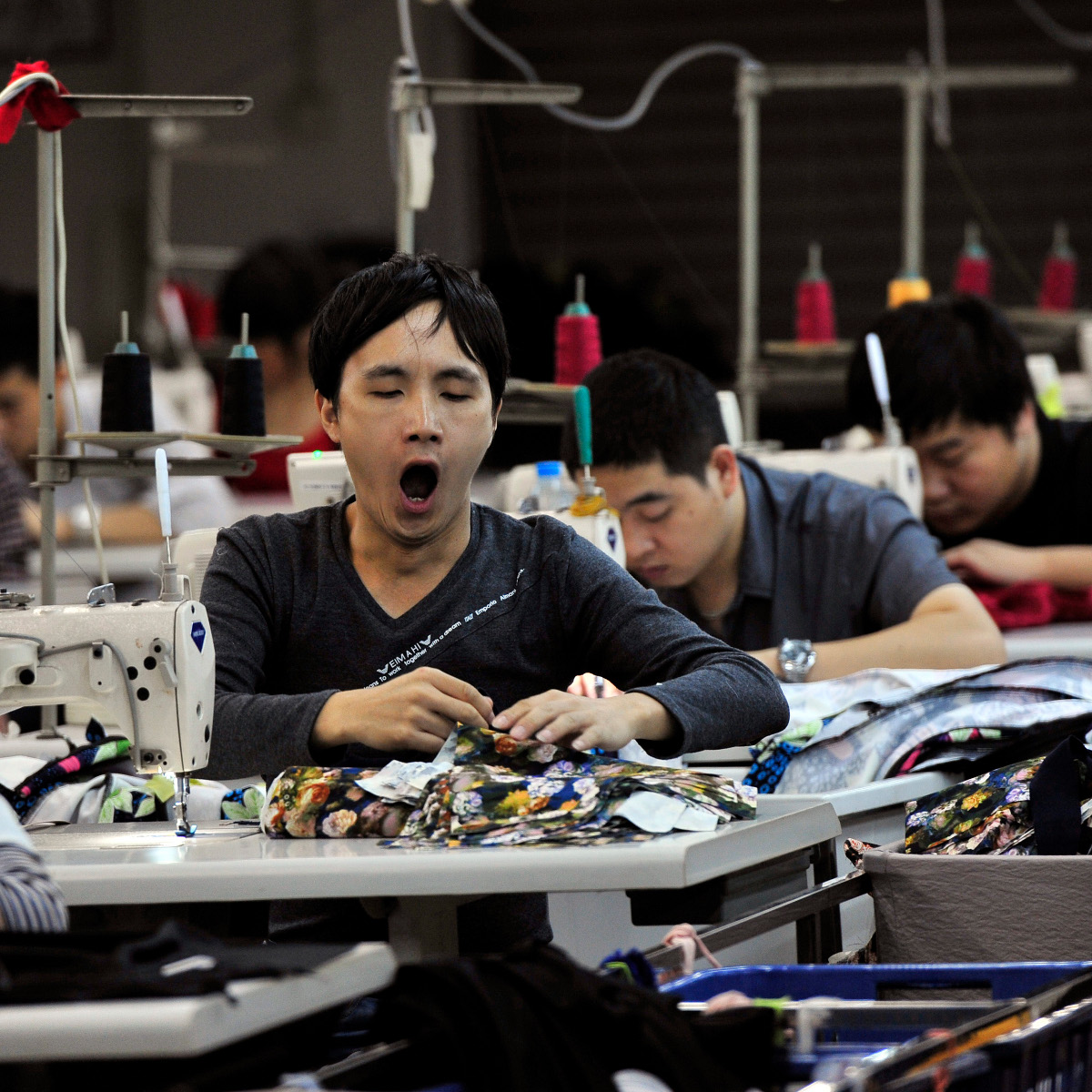 An employee yawns as he works at a garment factory in Humen township, Guangdong province November 24, 2013. Activity in China's vast factory sector grew at a milder pace in November as new export orders shrank, a preliminary survey showed on Thursday, bolstering expectations the economy could lose some of its vigour in the fourth quarter as Beijing shifts its focus to structural reform. Picture taken November 24, 2013.