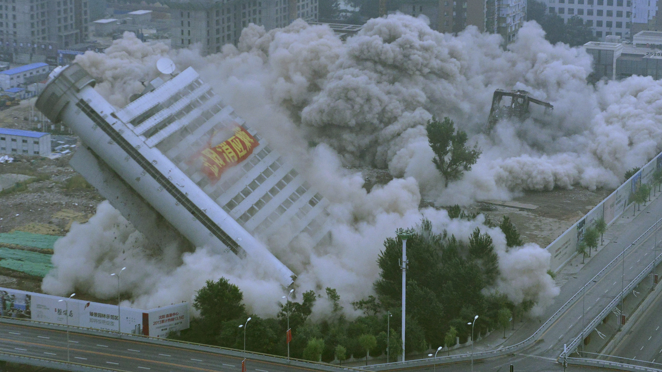 The building of Liaoning Province Meteorological Station topples near a residential construction site during a controlled demolition in Shenyang, Liaoning province September 29, 2013. The building, with a 45-metre-high giant thermometer attached to its exterior, was demolished to make way for a new residential area, local media reported. REUTERS/Stringer (CHINA - Tags: BUSINESS REAL ESTATE ENVIRONMENT CONSTRUCTION TPX IMAGES OF THE DAY)