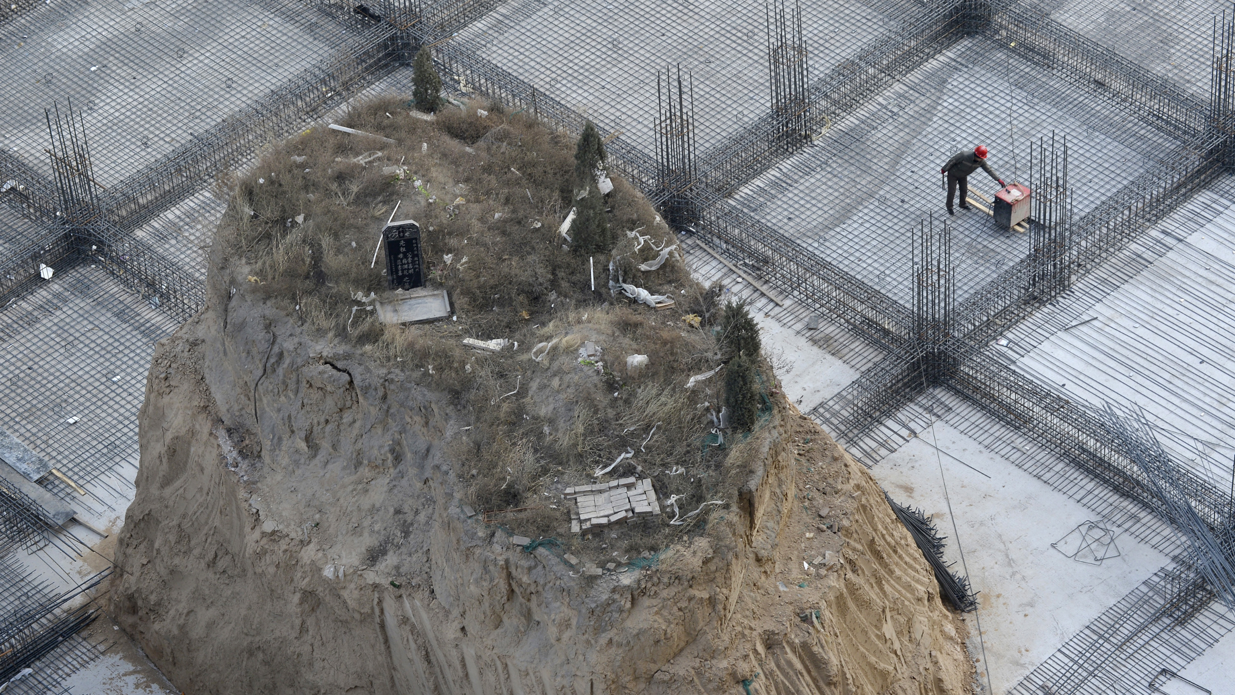 An ancestral tomb, measuring 10 metres high and a surface area of 10 square metres, is seen on the construction site of a building in Taiyuan, Shanxi province, December 6, 2012. The grave, which is believed to have existed since 2004, has not been moved as the family of the deceased is waiting for an auspicious date to do so and a reason from the developer of choosing this site, according to the owner of tomb. The building is scheduled to be completed by April 2013. REUTERS/Stringer