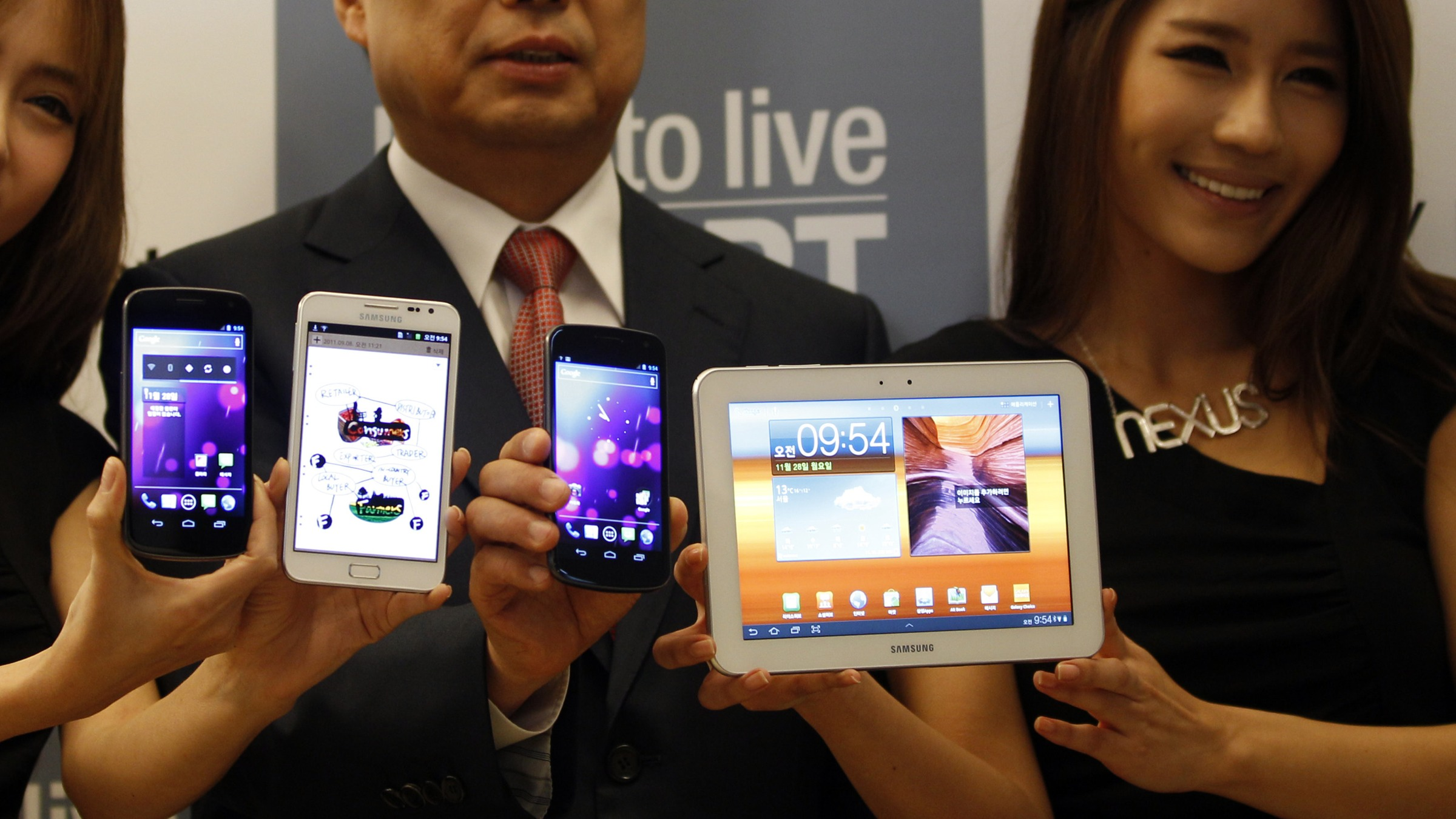 """Samsung Electronics mobile executive Shin Jong-gyun, center, and models display Samsung Electronics' newest devices Galaxy Note, second from left, which features the 5.29"""" Super Amoled screen and runs on the Android 2.3, Galaxy Nexus which features the 4.65 Super Amoled screen and runs on the Android 4.0, left and third from left, and the Galaxy Tab 8.9 LTE, right, during its unveiling ceremony in Seoul, South Korea, Monday, Nov. 28, 2011.(AP Photo/Lee Jin-man)"""