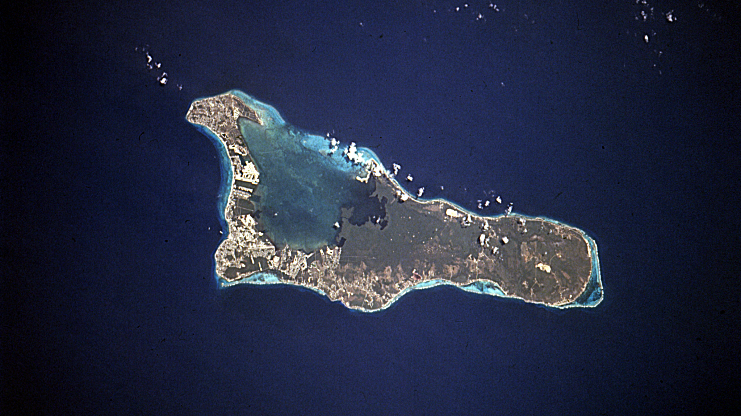 The island of Grand Cayman, a British dependency that covers 76 square miles (197 square kilometers) in the northwest Caribbean Sea, is visible in this near-vertical photograph. Geologically similar to The Bahamas, Grand Cayman is a low-lying, limestone island located on top of a submarine ridge. The city of George Town, the capital and chief port of the Cayman Islands, can be seen at the southwest end of the island. Grand Cayman's 7-mile beach can be seen on the western side of the island.