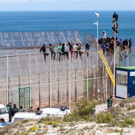 African migrants sit on top of a border fence covered in razor wire between Morocco and Spain's north African enclave of Melilla during their latest attempt to cross into Spanish territory, April 3, 2014. Spain has more than doubled the strength of security forces at Melilla, after about 500 people stormed its fences in the biggest border rush for years earlier this month. Immigrants from all over Africa regularly dare the razor-wire fences of Spanish enclaves Ceuta and Melilla, which are surrounded by Moroccan territory and sea.