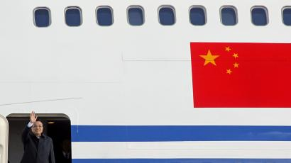 Chinese Premier Li Keqiang waves hand as he arrives at the Otopeni airport in Bucharest November 25, 2013. REUTERS/Bogdan Cristel