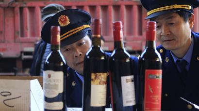 DATE IMPORTED:June 09, 2013Police officers check bottles of confiscated fake wines before destroying them in Xi'an, Shaanxi province January 4, 2012. Liquor stores, restaurants and supermarkets in China, the world's most populous nation and fifth-largest wine consumer, wage a constant battle against fake wines. The amount of knock-offs on the market may increase as Beijing investigates wine imports from the European Union, threatening anti-dumping tariffs or import curbs. Picture taken January 4, 2012. REUTERS/Stringe