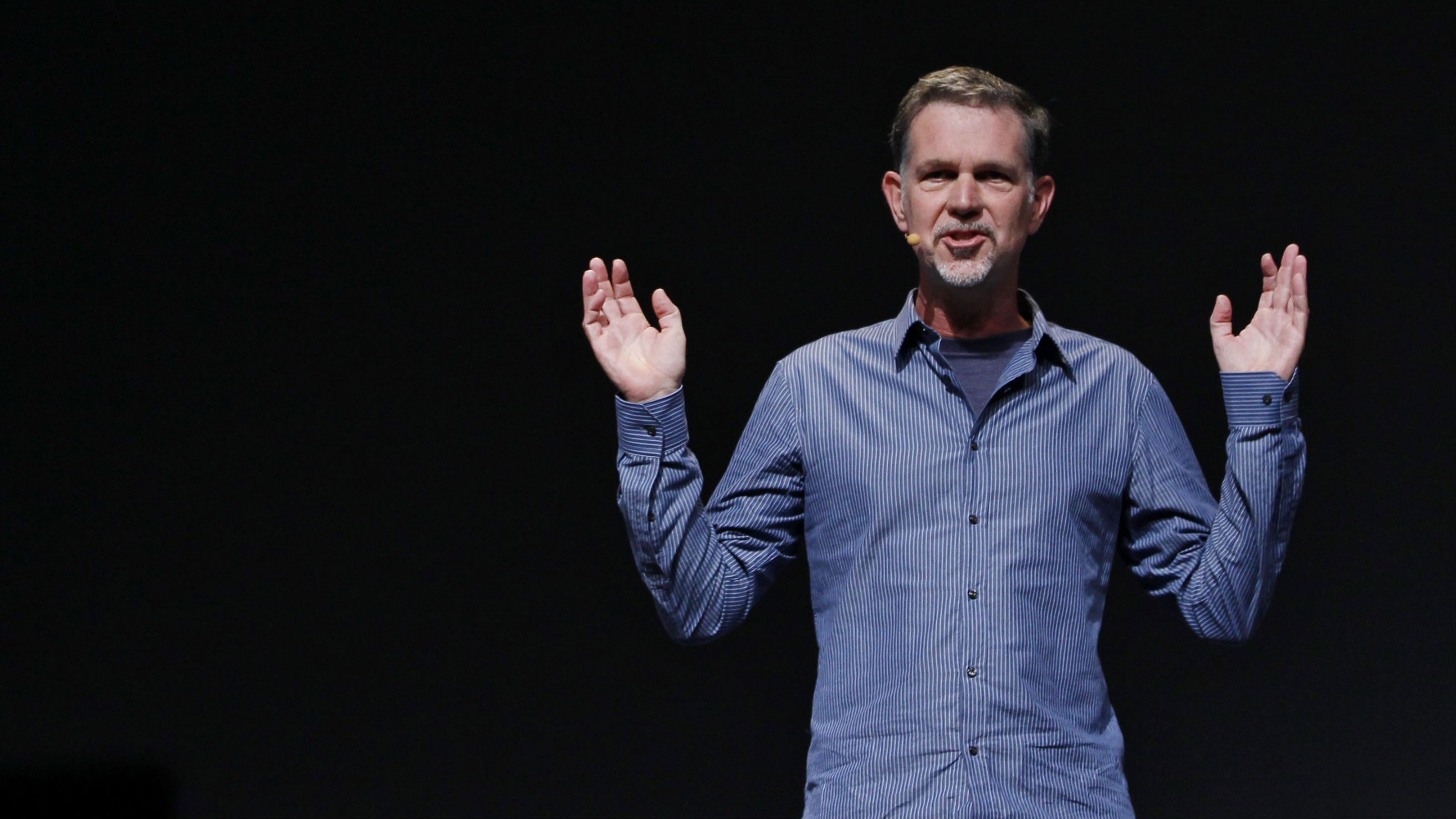 Reed Hastings of Netflix with his arms in the air