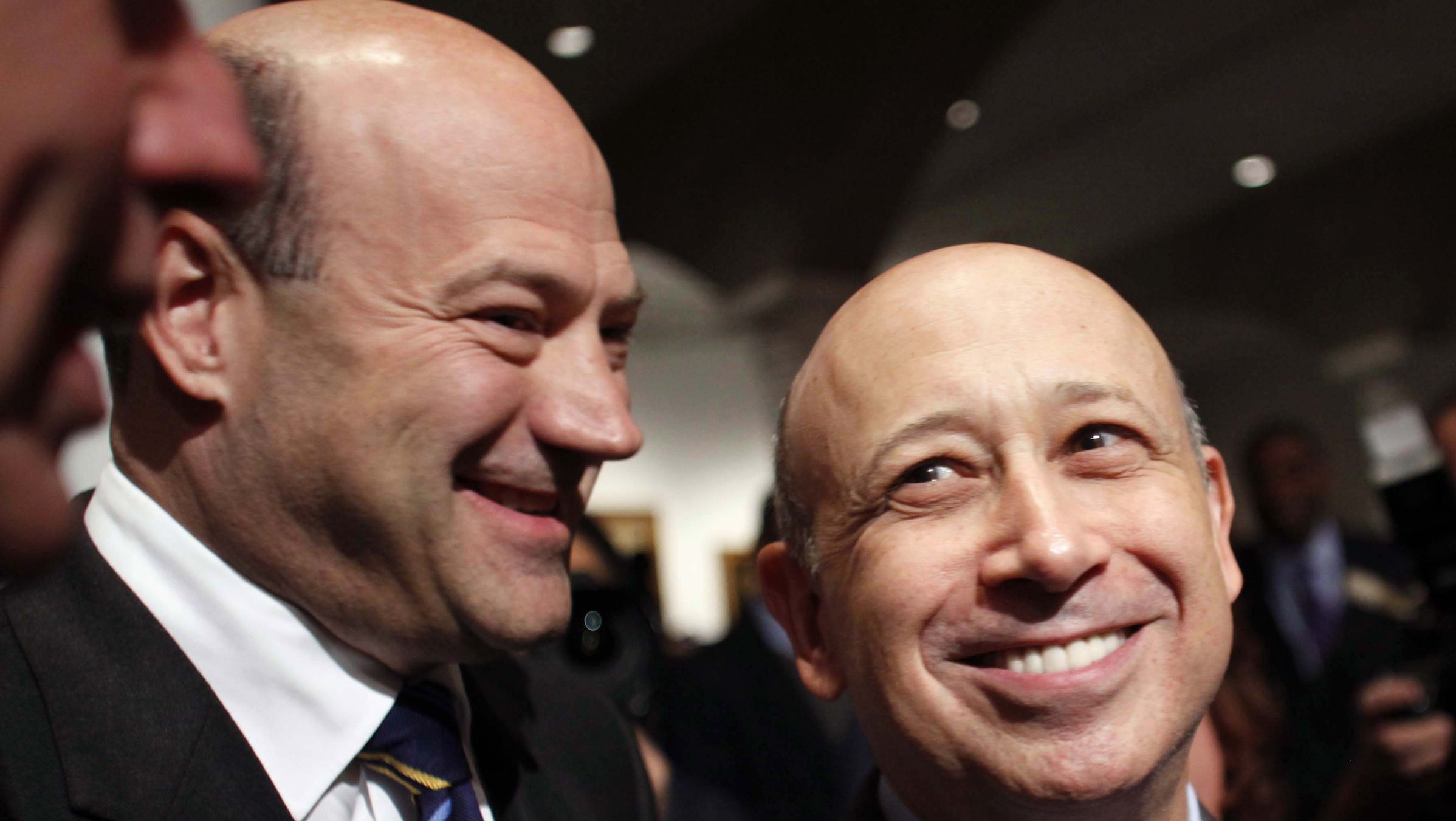 """Goldman Sachs CEO Lloyd Blankfein (R) and his colleague Gary Cohn (L), president and COO, attend a speech by U.S. President Barack Obama about new financial regulation at Cooper Union in New York April 22, 2010. Obama scolded Wall Street on Thursday for its """"furious efforts"""" to fight tighter regulation, saying the United States was doomed to another financial crisis if reforms were not implemented. REUTERS/Natalie Behring (UNITED STATES - Tags: POLITICS BUSINESS) - RTR2D4SN"""