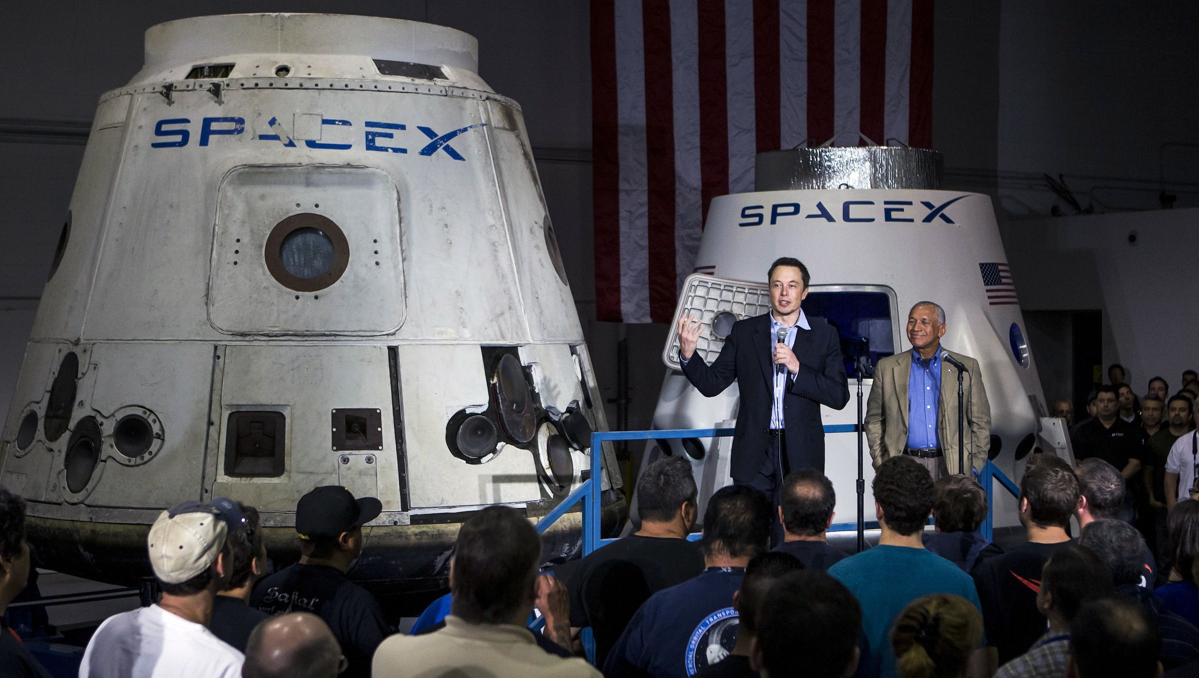 Elon Musk and a NASA exec talk about space exploration in front of a space capsule.