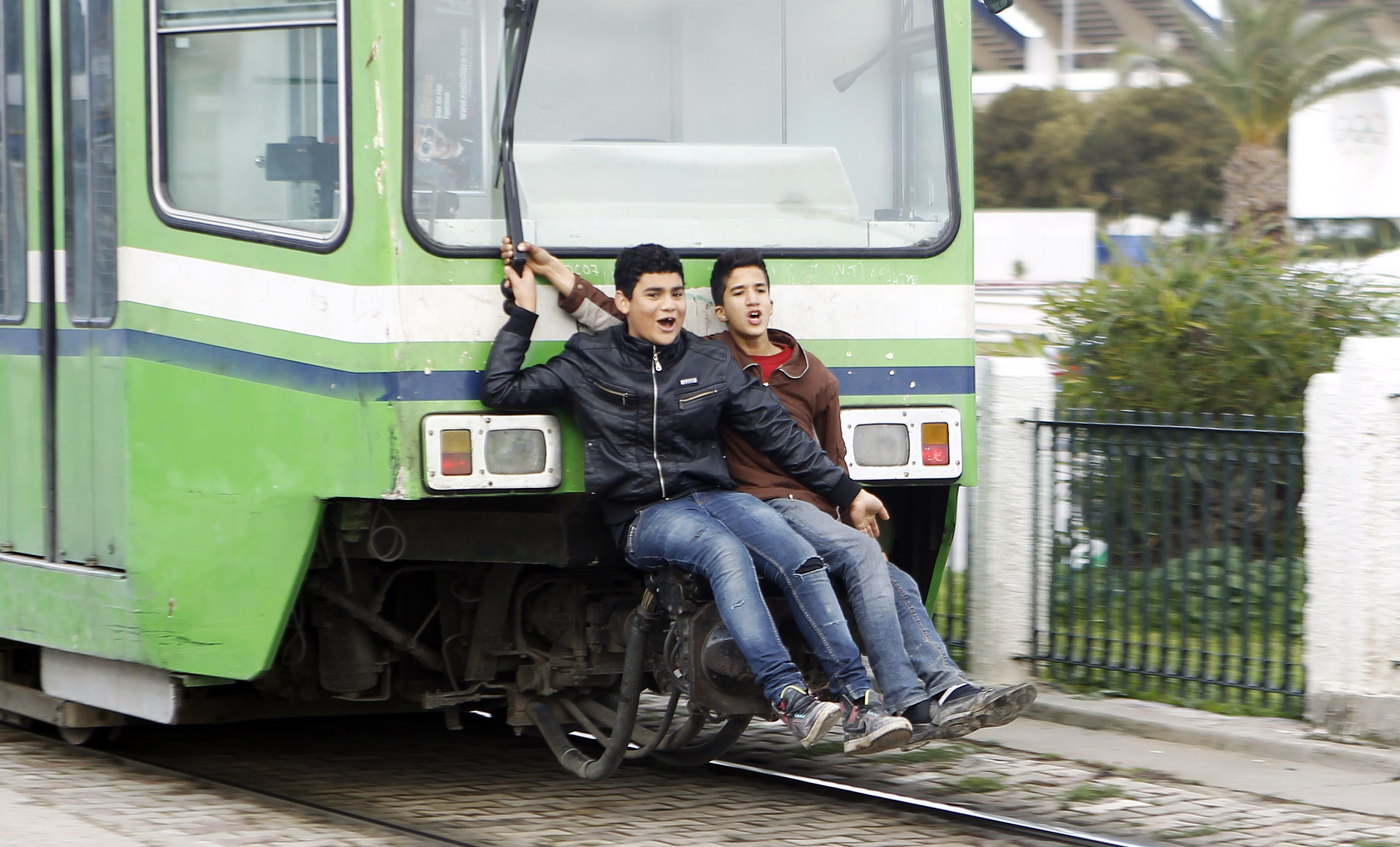 Boys ride on the back of a tram in Tunis February 5, 2013. REUTERS/ Zoubeir Souissi (TUNISIA - Tags: SOCIETY TRANSPORT) - RTR3DE31