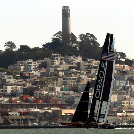 Oracle Team USA sails near the city skyline against Emirates Team New Zealand during Race 14 of the 34th America's Cup yacht sailing race in San Francisco, California September 22, 2013.