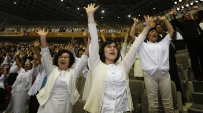 Believers of the Unification Church give three cheers as they attend the first death anniversary of evangelist Reverend Moon Sun-myung by the lunar calendar, in Gapyeong, about 60 km (37 miles) northeast of Seoul August 23, 2013. Moon, founder and head of the Unification Church with millions of followers around the world, died on September 3, 2012. Born in what is now North Korea in 1920, Moon founded the church soon after the Korean War that ended in 1953, rapidly expanding the ministry internationally and building a business at the same time that served as the backbone of the empire. REUTERS/Lee Jae-Won