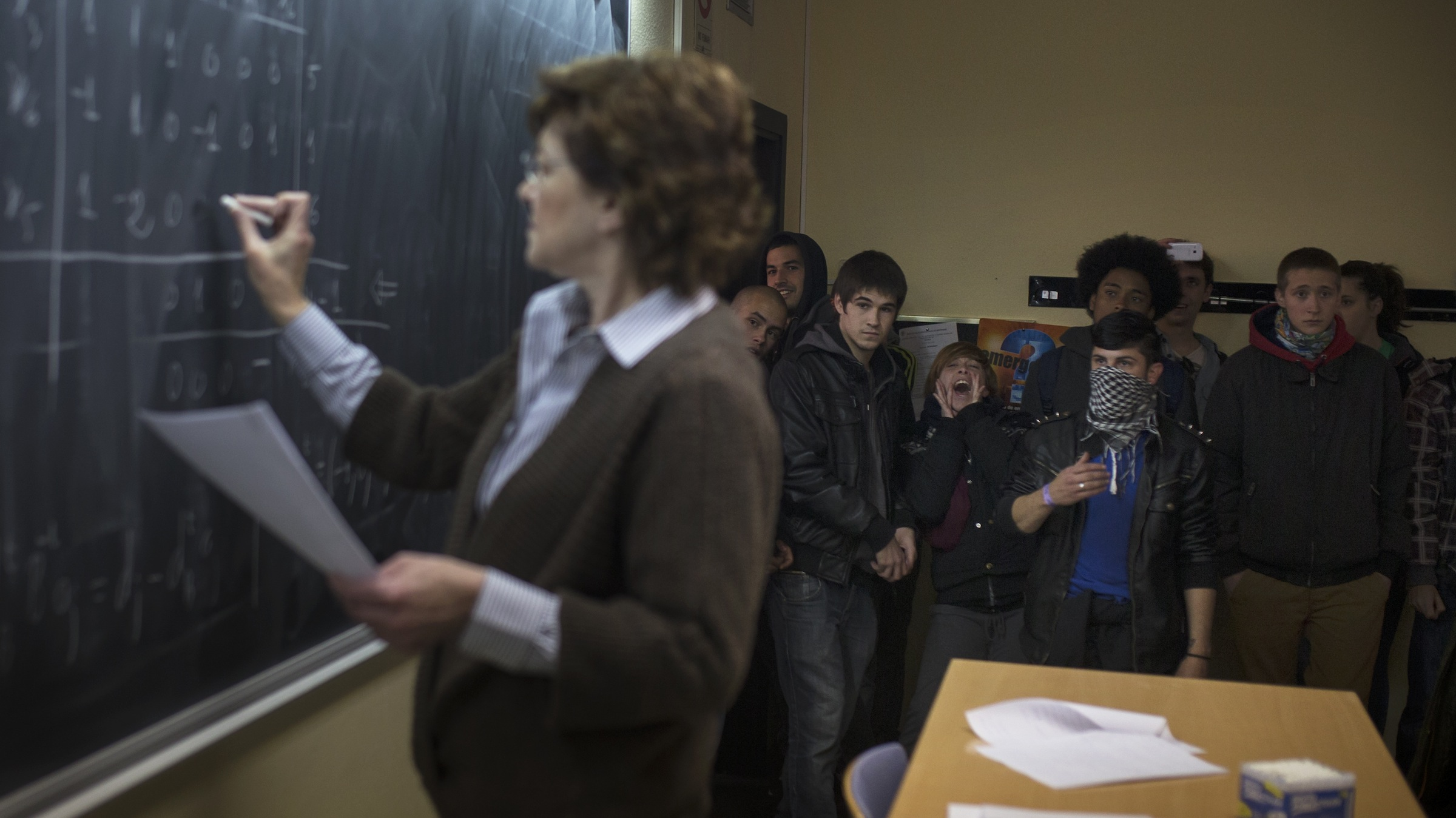 Protestors enter a classroom , as a teacher, left, gives a lecture during the second day of student strikes to protest against the government education reform and cutbacks in grants and staffing, at Complutense University in Madrid, Spain, Thursday, March 27, 2014. (AP Photo/Andres Kudacki)