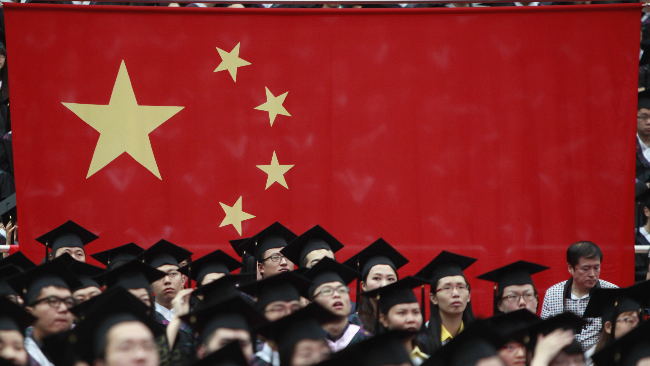 Graduates set next to the Chinese flag during a graduation ceremony at Fudan University in Shanghai June 28, 2013. A record high of 6.99 million students are expected to graduate from college this year which places severe pressure on their search for jobs, according to Xinhua News Agency. REUTERS/Aly Song