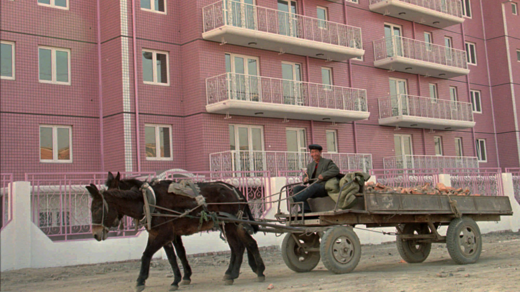 A donkey-wagon carries the rubble past a modern apartment building under construction in Beijijg Thursday, Dec. 21, 1995. Construction for hotels and apartment buildings are booming in China. (AP Photos/Sadayuki Mikami