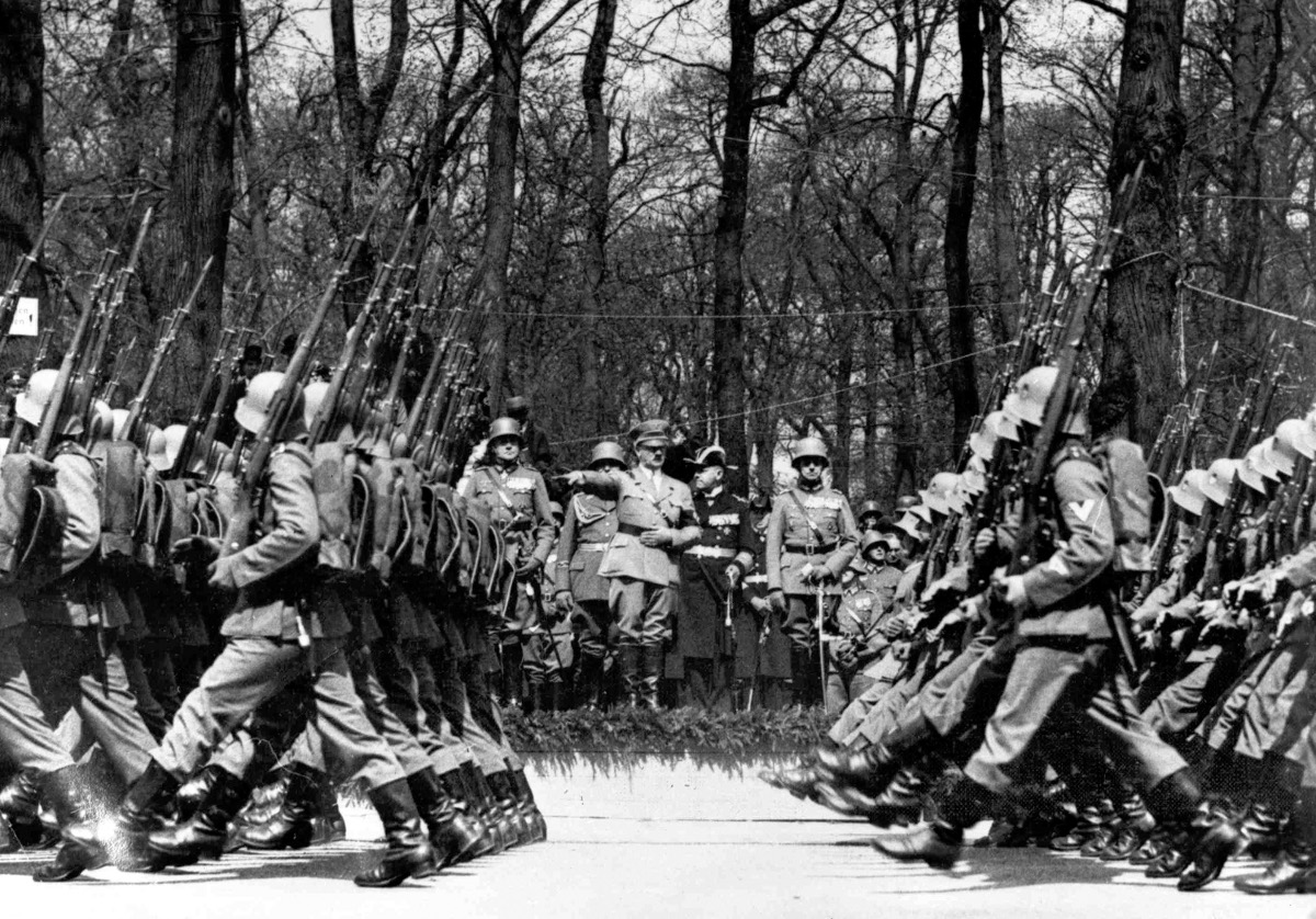 In this April 20, 1936 file photo, armed troops march past German Chancellor Adolf Hitler during a parade in Berlin to celebrate his birthday. As the Nazis increasingly targeted Jews and others they considered enemies, they moved in 1938 to loosen gun statutes for the loyal majority, said Bernard Harcourt, a University of Chicago professor of law and political science who has studied gun regulations under Hitler. The 1938 law is best known for barring Jews from owning weapons, after which the Nazis confiscated guns from Jewish homes. But Harcourt points out that Hitler's gun law otherwise completely deregulated acquisition of rifles, long guns and ammunition. It exempted many groups from requiring permits. The law lowered the age for legal gun ownership from 20 to 18. And it extended the validity of gun permits from one year to three years.