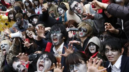 People, dressed as zombies, pose for photos after the Roppongi Zombie Walk in Tokyo March 31, 2013. About 50 people dressed up as zombies early evening on Sunday, catching the attention of pedestrians on the streets of Tokyo's downtown Roppongi district. REUTERS/Yuya Shino