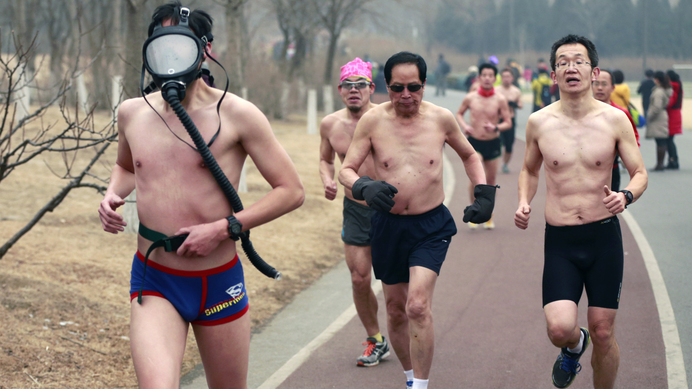 "A half-naked participant wears a gas mask as he takes part in the ""Guangzhu (naked) Run"" with others on a hazy winter morning at the Olympic Forest Park in Beijing, February 23, 2014. Beijing's running enthusiasts joined this event, which required them to run wearing only their underwear, as a way to promote environmentally-friendly lifestyles, on Sunday morning under an orange alert of air pollution, local media reported. REUTERS/China Daily"