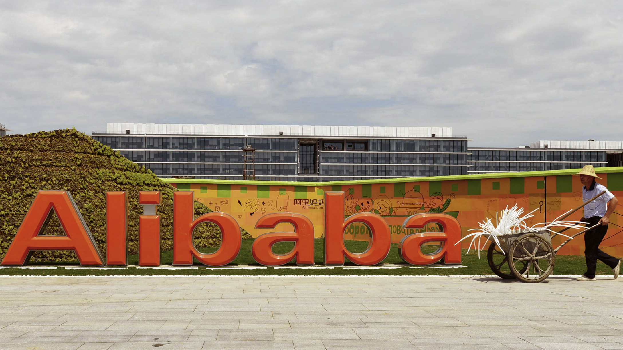A worker walks past a logo of Alibaba Group at its headquarters on the outskirts of Hangzhou, Zhejiang province, August 24, 2013. China's e-commerce market is expected to leapfrog that of the United States this year to become the world's largest by total customer spending, management consultancy firm Bain & Company says, and could account for half of all Chinese retail spending within a decade. Picture taken August 24, 2013. REUTERS/China Daily