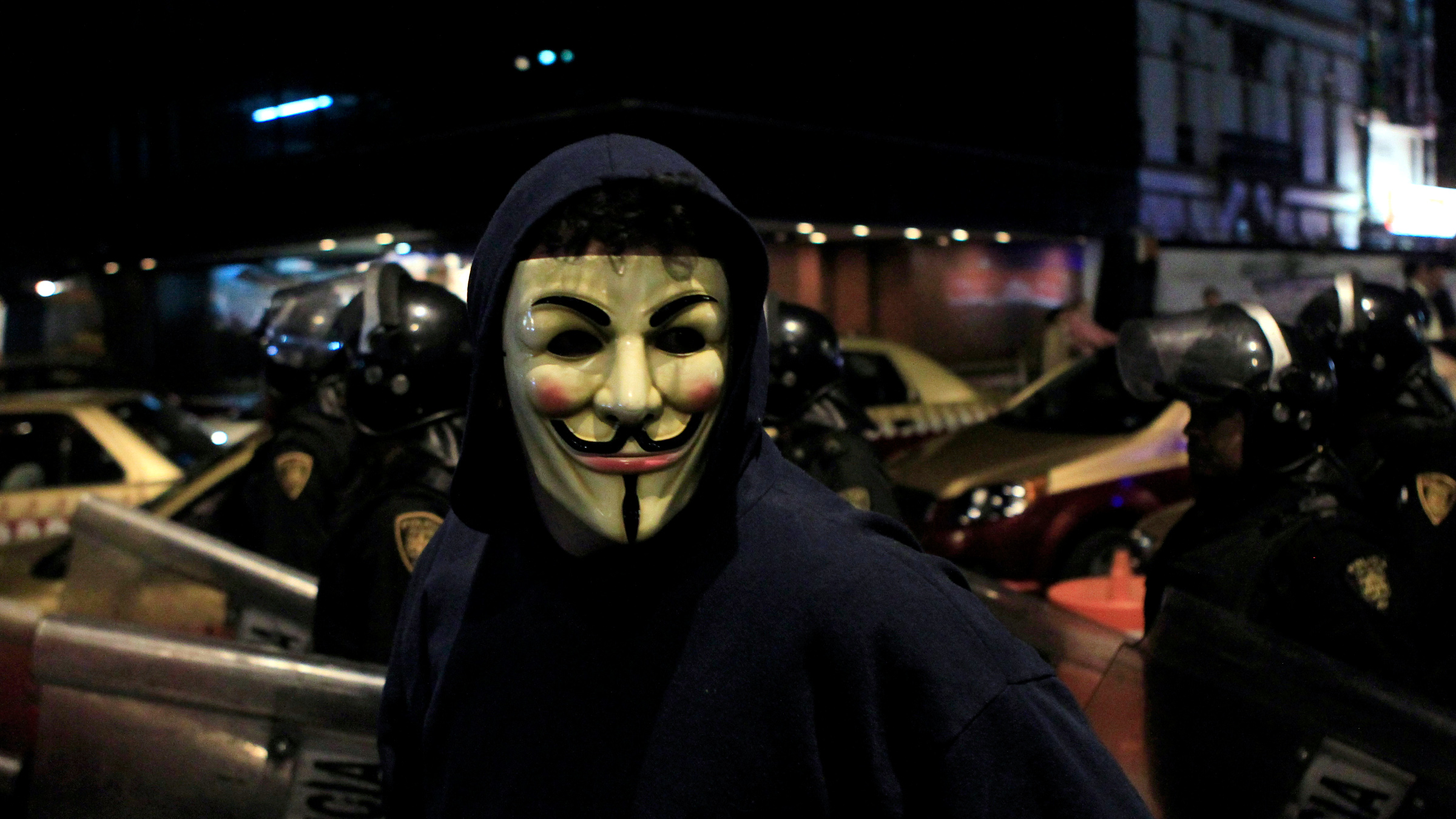 """A protester wearing a Guy Fawkes mask walks past riot police during a demonstration by supporters of the Anonymous movement as part of the global """"Million Mask March"""" protests in Mexico City November 5, 2013."""