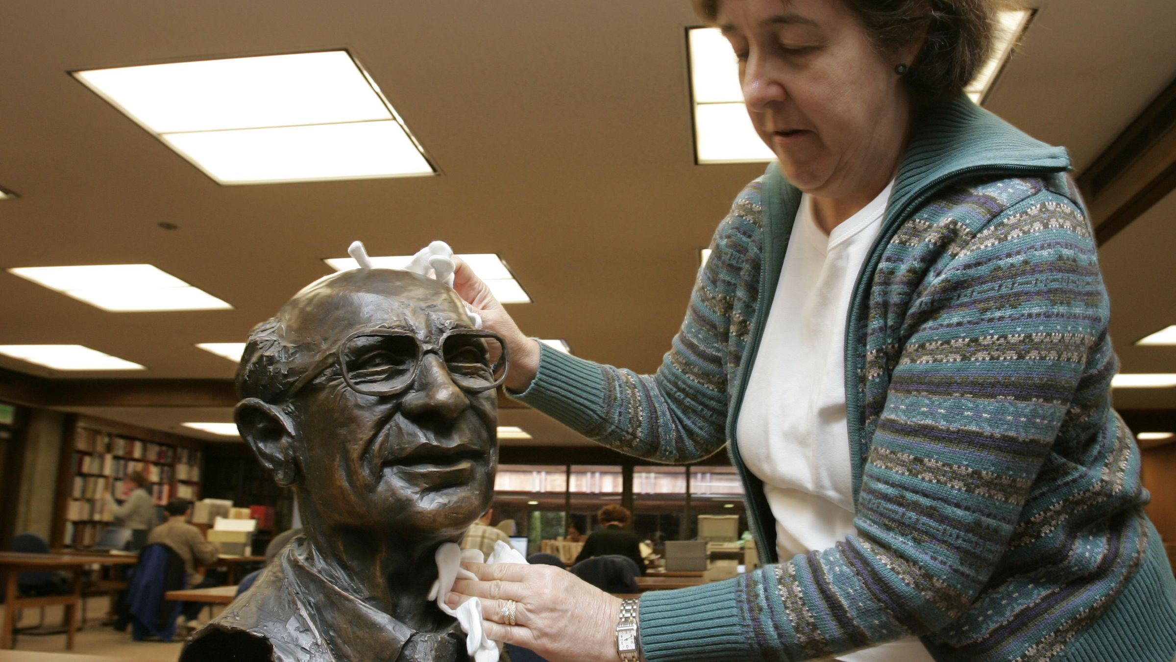 Carol Leadenham, an archivist for the Hoover Institute on the Stanford University campus, cleans the bust of  Milton Friedman, the Nobel Prize-winning economist who advocated an unfettered free market and had the ear of three U.S. presidents, on display in a reading room in Stanford, Calif., Thursday, Nov. 16, 2006. Friedman died in San Francisco, Thursday, Nov. 16, 2006 at age 94. (AP Photo/Paul Sakuma)