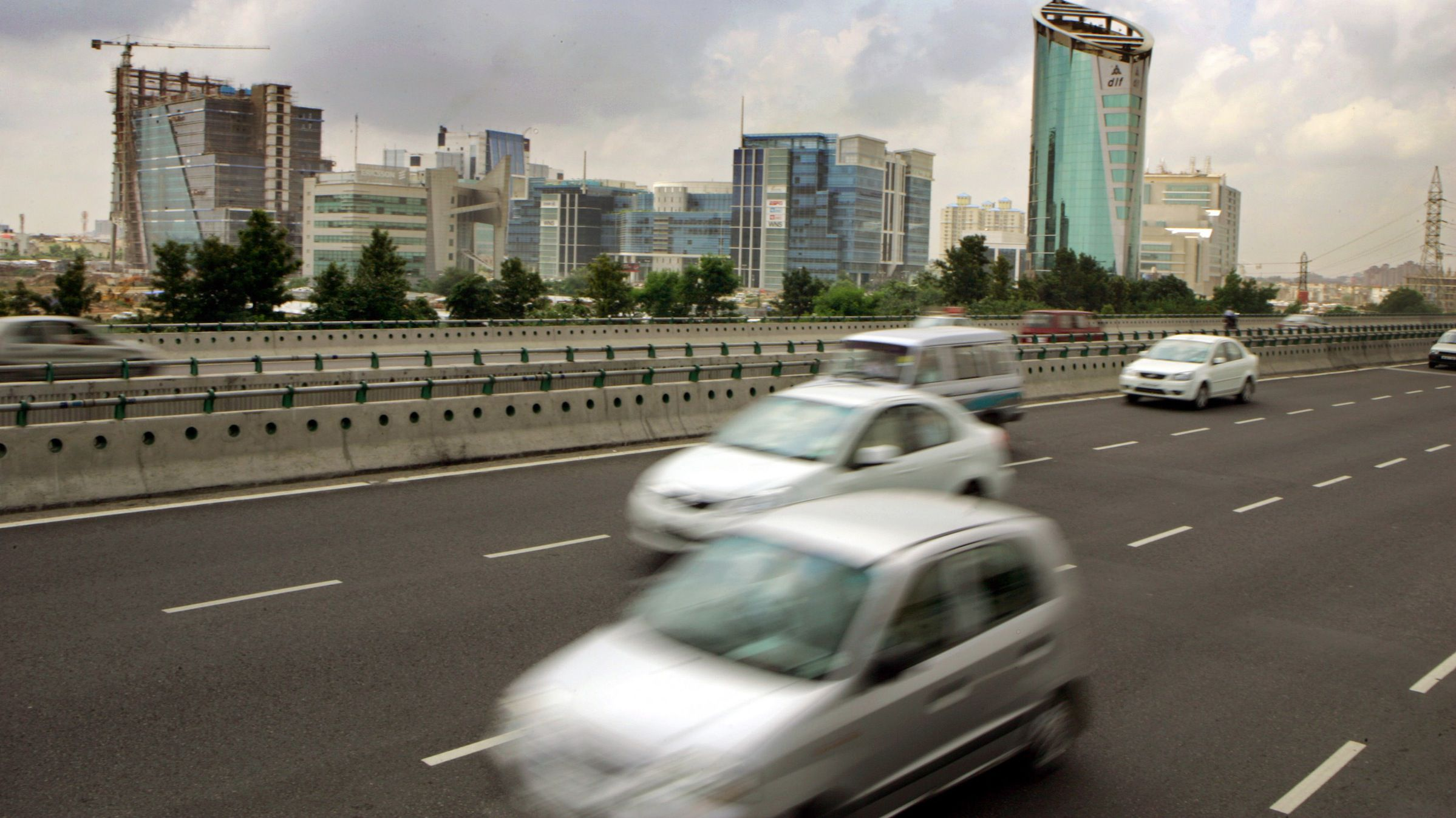 Rush hour traffic moves next to an expressway in the backdrop of office complexes in Gurgaon, India, Aug. 6, 2007. Sixty years ago this month, India and Pakistan won their Independence, now Pakistan, no stranger to domestic turmoil, is embroiled in an increasingly violent struggle between Islamic extremists and moderates, where as India is racing to become an economic powerhouse, lightning growth has transformed the country and fueled a consumer boom. (AP Photo/Gurinder Osan)
