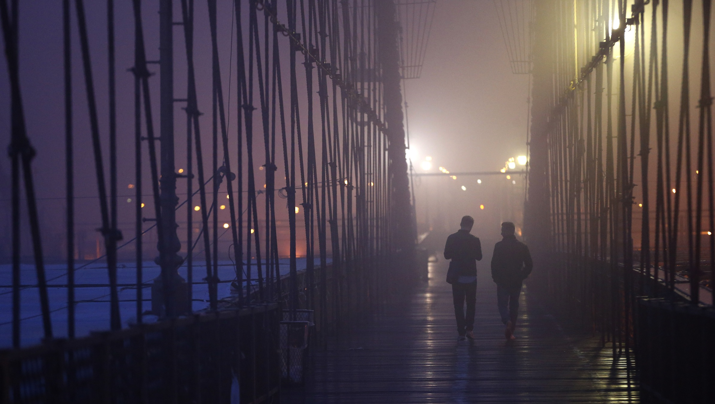 Swiss tourists Philipp Klausner, left, and Marco Varmettler walk on the Brooklyn Bridge as early morning fog covers New York City, Saturday, May 10, 2014. (AP Photo/Julio Cortez)
