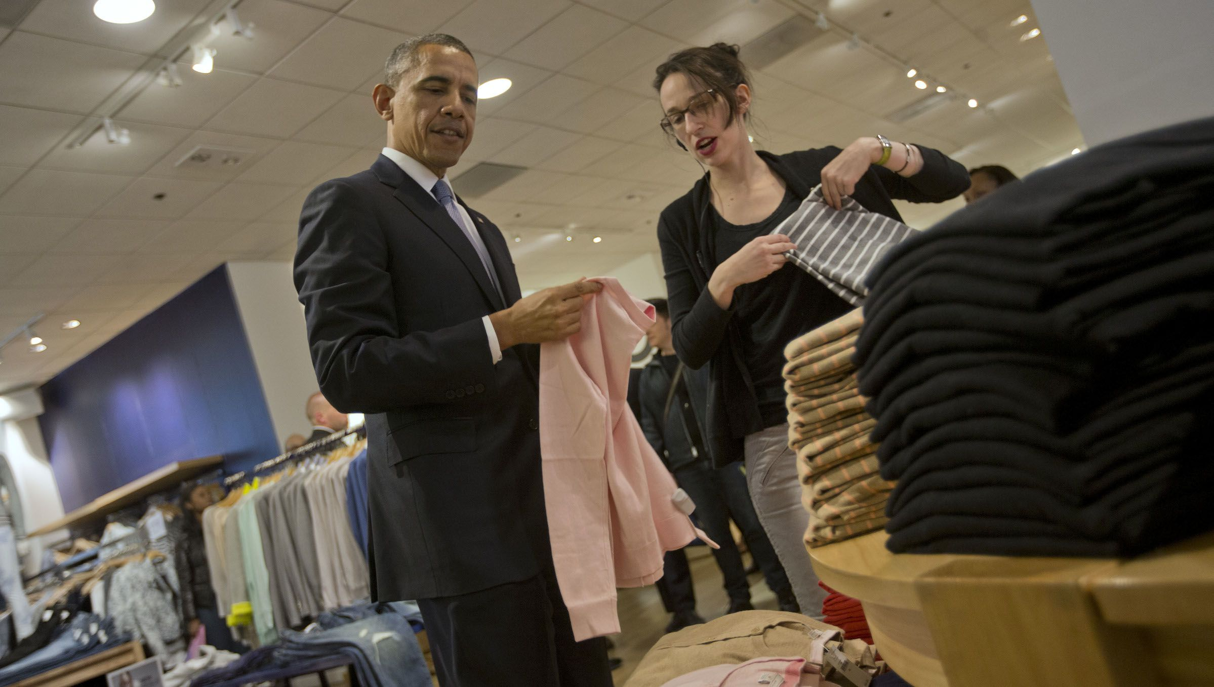 President Barack Obama, center, with the help of store employee Susan Panariello, shops for sweaters at GAP clothing store in Manhattan during his unannounced visit, Tuesday, March 11, 2014 in New York. Obama used the visit to talk about raising the minimum hourly wage standards and applauded the GAP, who earlier in the year announced it was raising minimum wage for its employees. (AP Photo/Pablo Martinez Monsivais)
