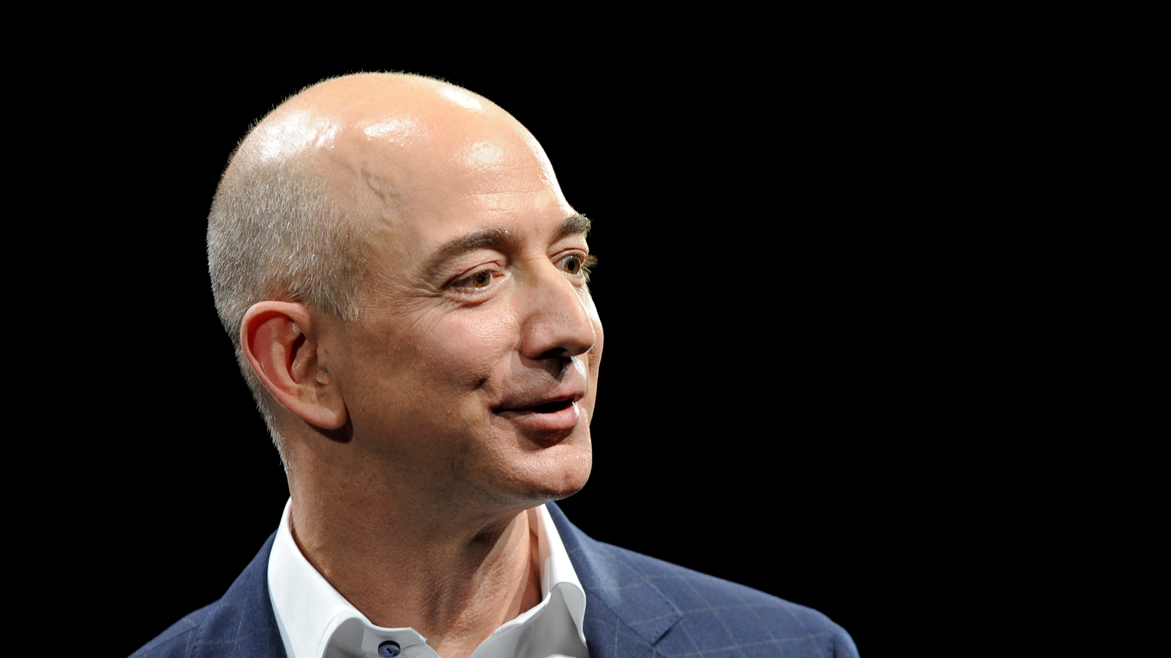 Amazon CEO Jeff Bezos demonstrates the Kindle Paperwhite during Amazon's Kindle Fire event in Santa Monica, California September 6, 2012. Amazon.com Inc unveiled a larger, high-speed Kindle Fire tablet on Thursday for $499, challenging Apple Inc's dominant iPad and intensifying a battle with Google Inc and Microsoft in the booming tablet arena.  REUTERS/Gus Ruelas