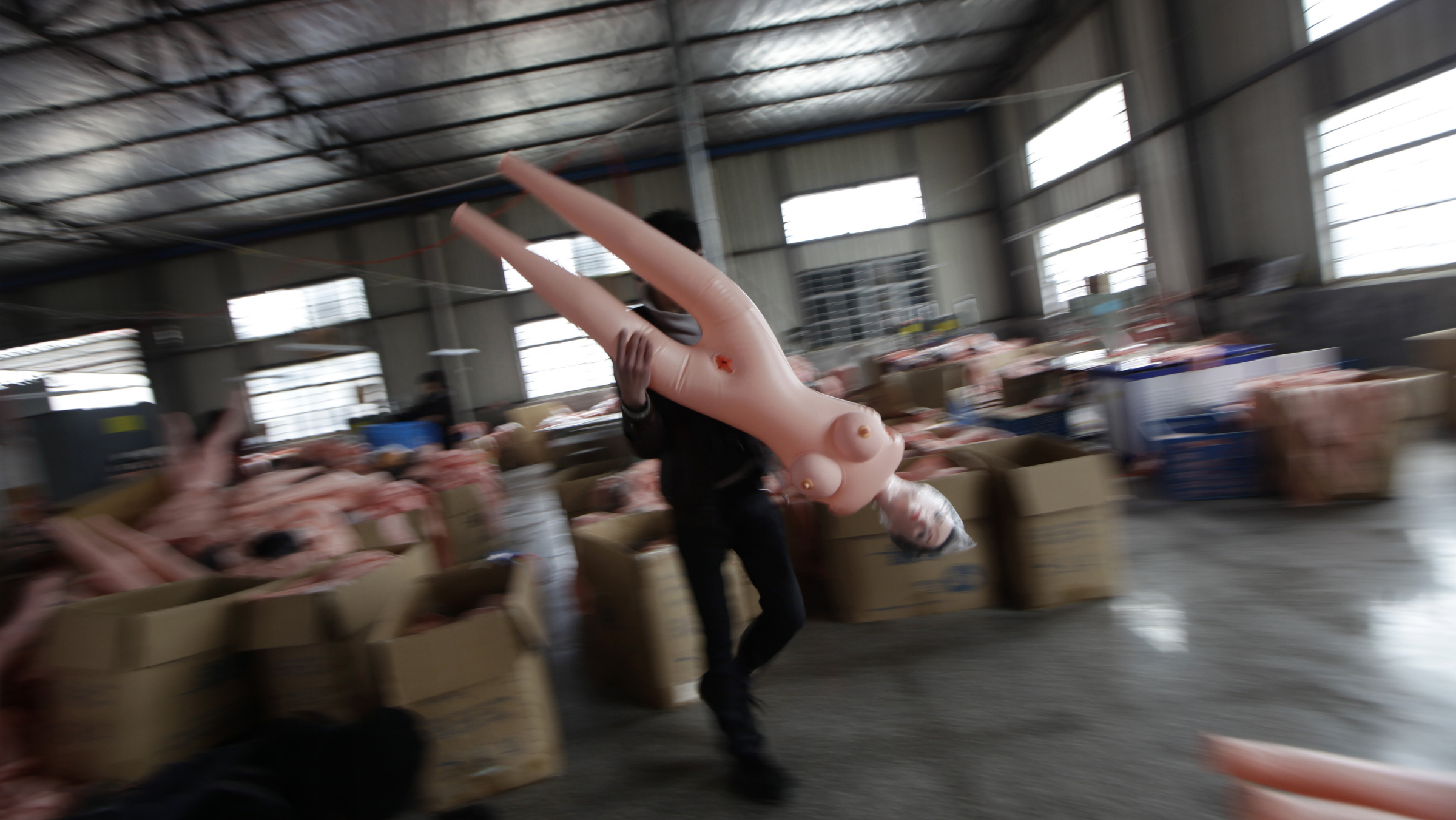 A worker moves an inflatable sex doll at Ningbo Yamei plastic toy factory, on the outskirts of Fenghua, Zhejiang province, February 13, 2012. The company started producing sex dolls three years ago, and now owns a total of 13 types of dolls at the average price of 100 RMB (16 USD). More than 50,000 sex dolls were sold last year, about fifteen percent of which were exported to Japan, Korea and Turkey, according to the company. REUTERS/Jason Lee