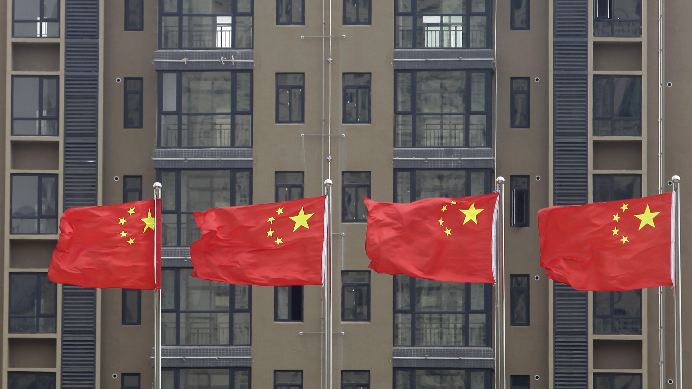 Chinese national flags fly in front of a newly-built residential apartment in Wuhan, Hubei province July 10, 2012. China must firmly maintain its property tightening measures to cool housing prices, Premier Wen Jiabao was quoted as saying on Saturday, underscoring official concerns about renewed bubbles as the central bank ratchets up policy easing to support growth. REUTERS/Stringer