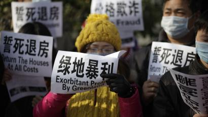 Dozens of homeowners protest outside the headquarters of a Chinese property developer over discounts that came after they paid for their own apartments in Shanghai, China, on Friday, Dec. 16, 2011. The government has said it will keep policies aimed at cooling the property market in place to help bring prices down to more affordable levels, but news that first-time homeowners may be allowed lower-interest mortgages may signal an easing for real estate developers stressed by tight credit and falling sales. (AP Photo/Eugene Hoshiko