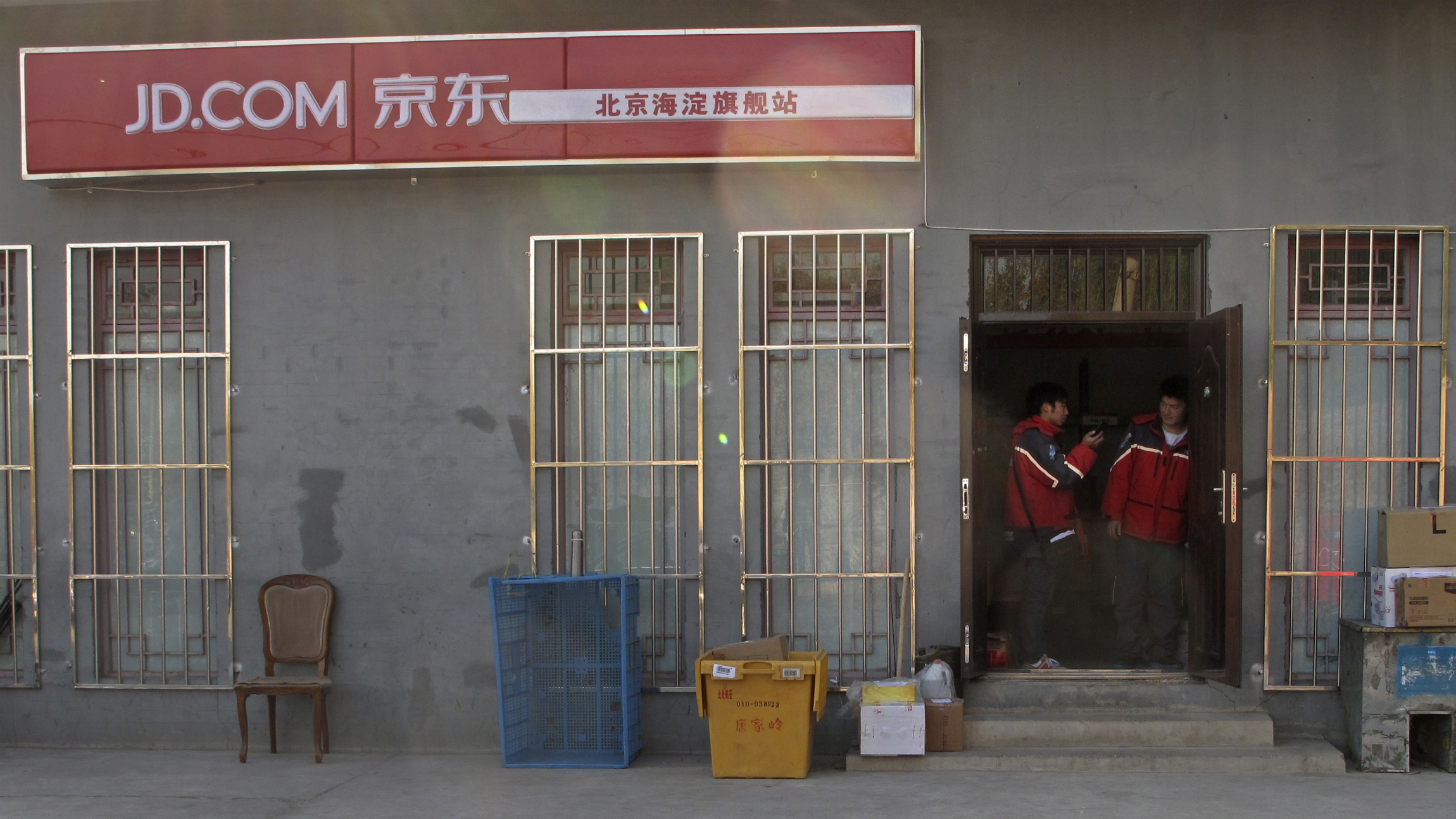 Two Jingdong, also known as JD.com, couriers chat at the entrance to the company's Haidian district delivery station in Beijing, November 20, 2013. The Beijing-based firm, China's second largest e-commerce company, operates its own network of couriers and warehouses, a factor it says ensures timely and efficient delivery. Larger rivals Tmall and Taobao, the online marketplaces run by mega-firm Alibaba Group Holding Ltd, still depend on merchants and external courier firms for their logistics. Jingdong uses a 10,000-strong fleet of couriers to deliver packages to major locations across China within 24 hours. The company also has 1,400 warehouses nationwide to supply a customer base that accounts for over a sixth of China's 591 million registered Internet users. Picture taken November 20, 2013. REUTERS/Paul Carsten