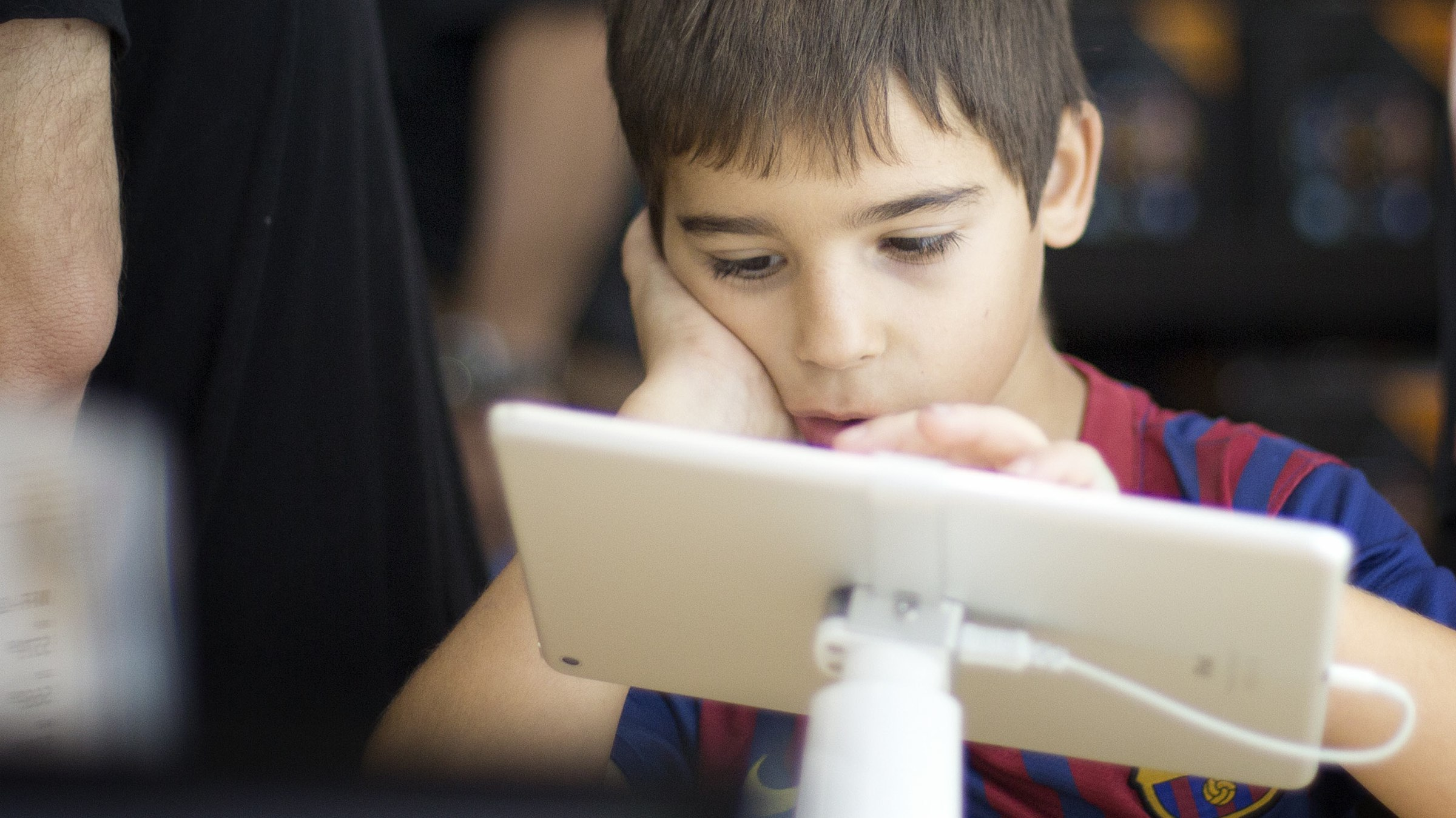 Jacob Blacker plays with an iPad, the type he wants for the Christmas holiday, as his dad shopped for a tablet at the Pembroke Pines, Fla. Best Buy store, Friday, Nov. 29, 2013. Black Friday, the day after Thanksgiving, is the nation's biggest shopping day of the year.  (AP Photo/J Pat Carter)