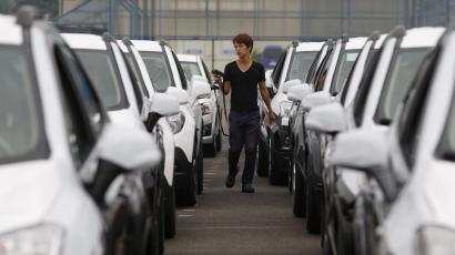 A worker checks cars made by GM Korea in a yard of GM Korea's Bupyeong plant before they are transported to a port for export, in Incheon, west of Seoul August 9, 2013. General Motors Co. has begun gradually cutting its presence in South Korea after mounting labor costs and militant unionism triggered a rethink of its reliance on the country for a fifth of its global production, three individuals familiar with GM's thinking said. Picture taken August 9, 2013. REUTERS/Lee Jae-Won