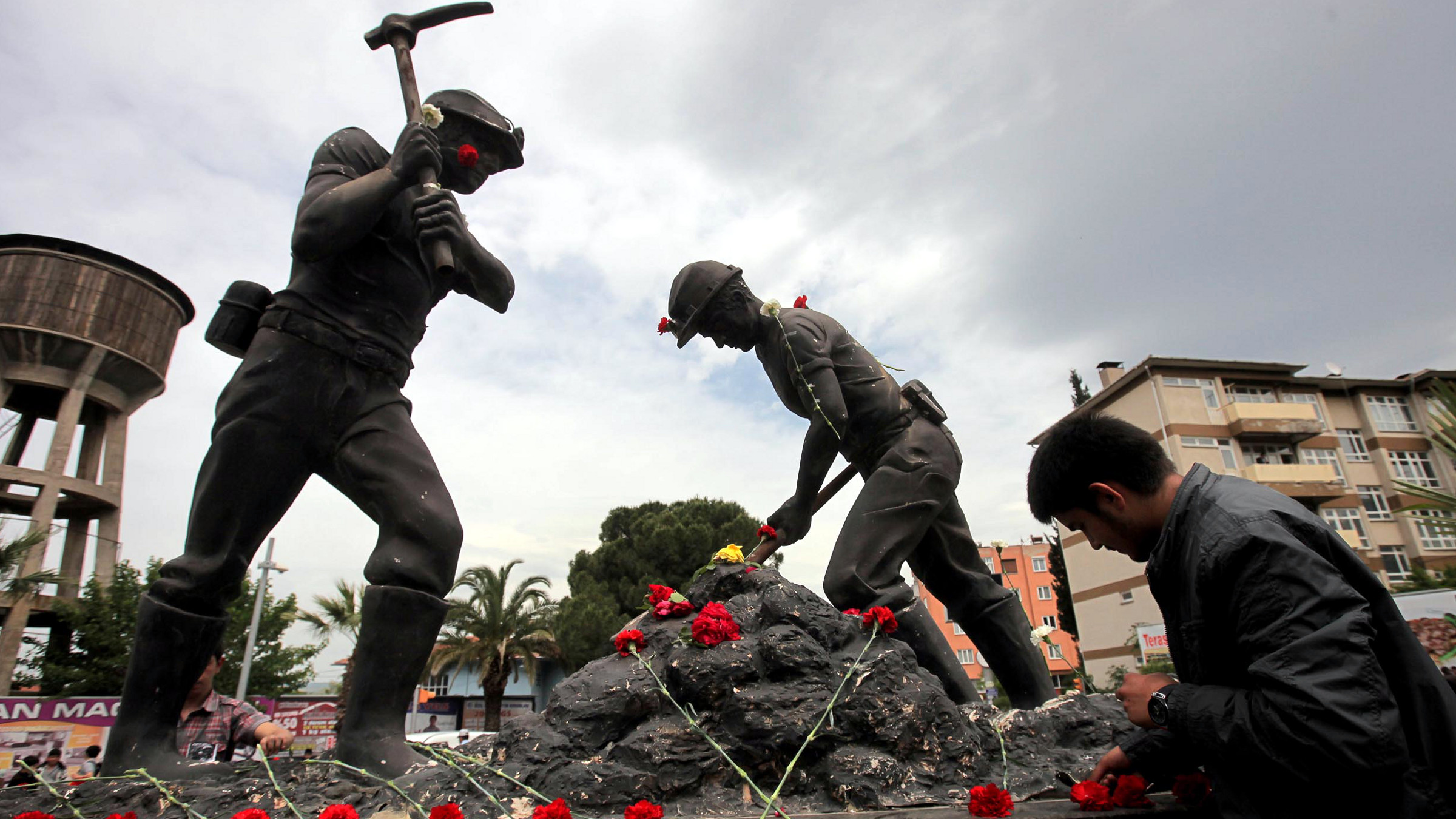 A man lays carnations at the Miners Monument in central Soma, a district in Turkey's western province of Manisa May 14, 2014. Rescuers pulled more dead and injured from the coal mine in western Turkey on Wednesday more than 12 hours after an explosion, bringing the death toll to above 200 in the nation's worst mining disaster for decades. Hundreds more were still believed to be trapped in the mine in Soma, around 120 km (75 miles) northeast of the Aegean coastal city of Izmir. The explosion, which triggered a fire, occurred shortly after 3 pm (1200 GMT) on Tuesday.