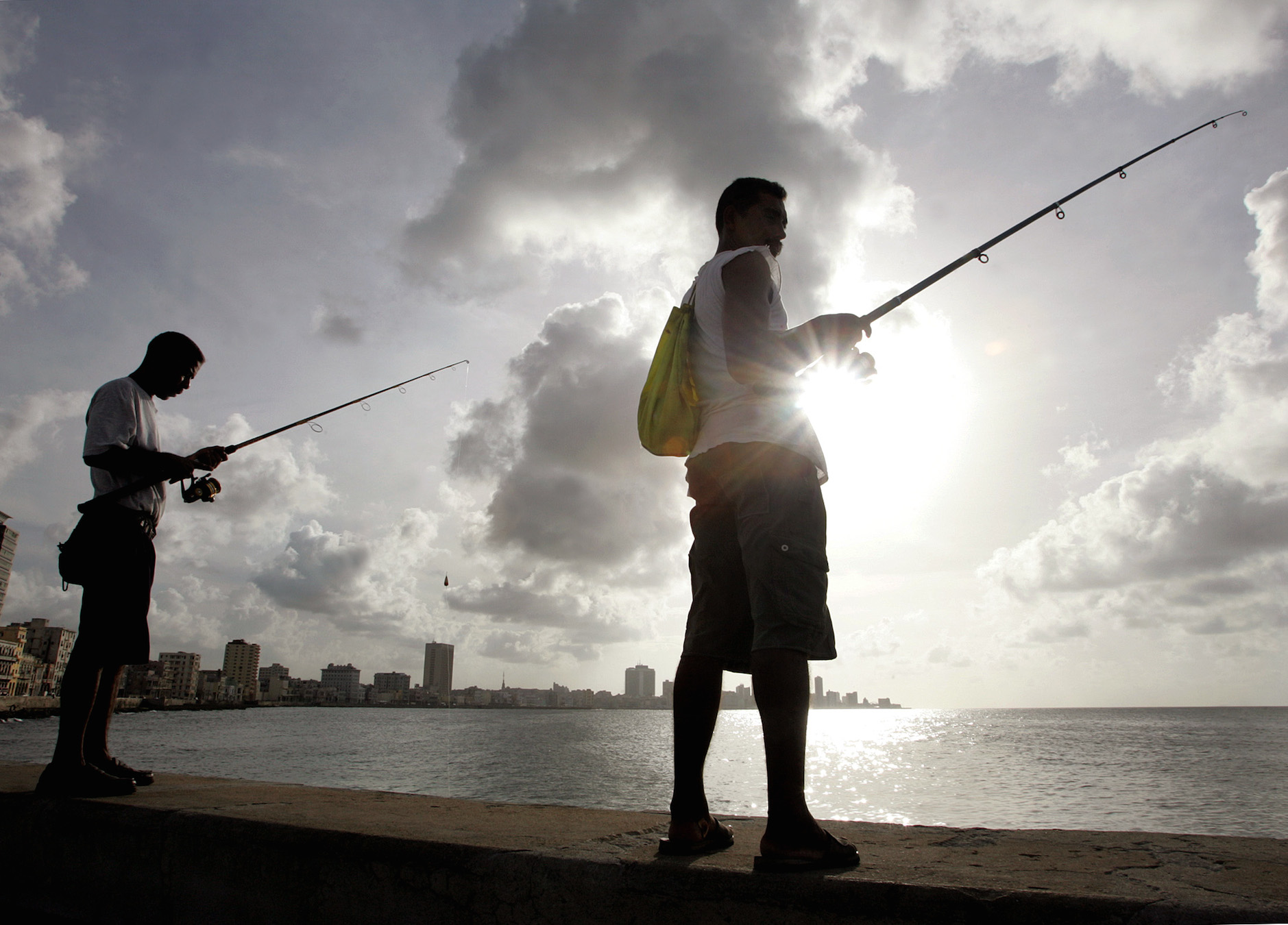 Cubans stand on the Malecon oceanfront as they fish in the glassy-calm waters, in spite of the approaching of Hurricane Ivan, September 10, 2004. Thousands of Cubans are getting ready to be evacuated from the island's southern side, as forecasters predict the worst hurricane in 60 years to hit Cuba could arrive here by Sunday. REUTERS/Claudia Daut NO RIGHTS CLEARANCES OR PERMISSIONS ARE REQUIRED FOR THIS IMAGE  CD - RTRAHB1