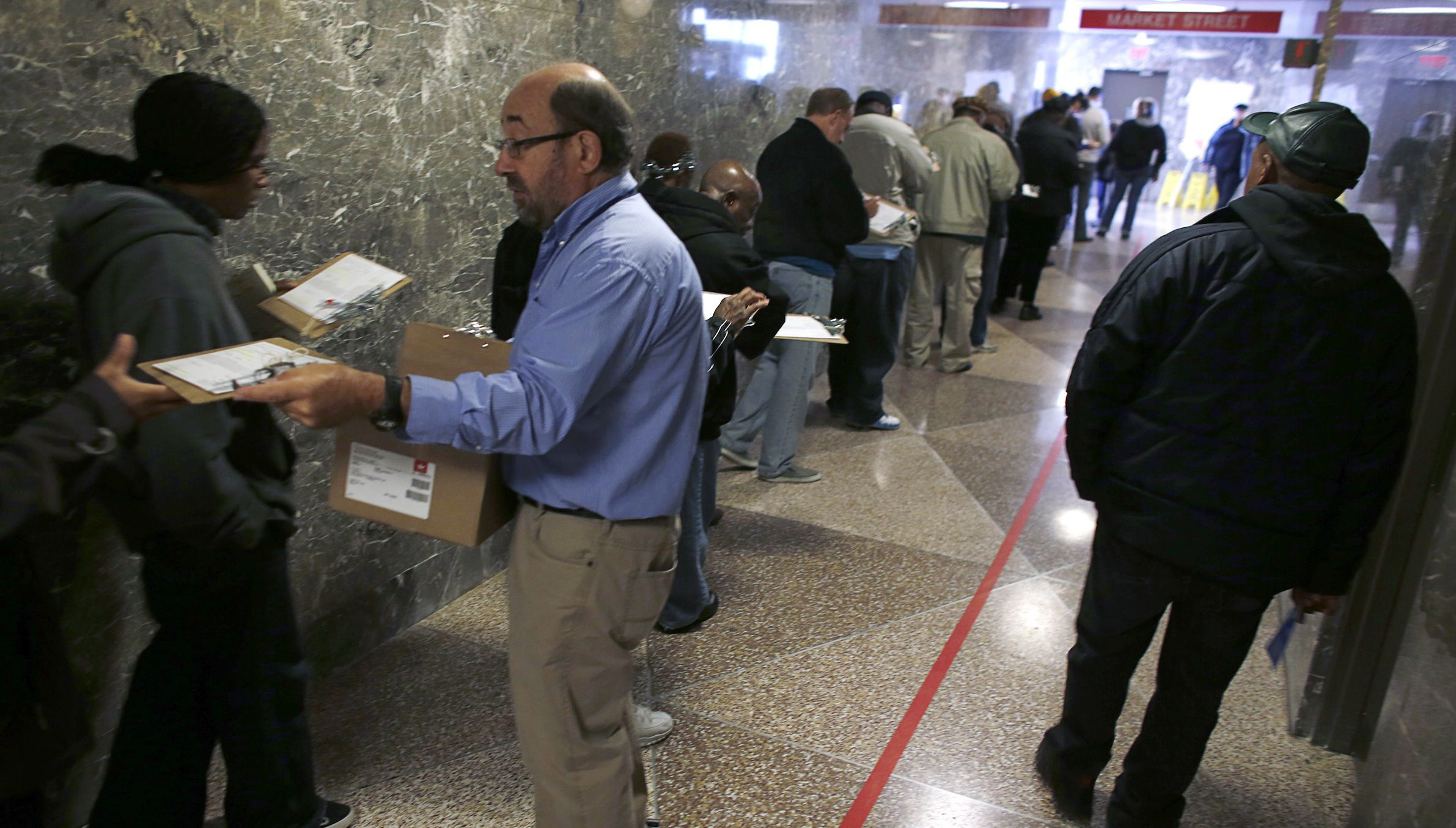 An election worker (in blue) hands out clipboards to residents waiting in line during the lunch hour to cast their early votes in the upcoming U.S. presidential elections, at the Milwaukee Municipal Building in Milwaukee, Wisconsin October 29, 2012. REUTERS/Darren Hauck (UNITED STATES - Tags: POLITICS ELECTIONS USA PRESIDENTIAL ELECTION) - RTR39R2I