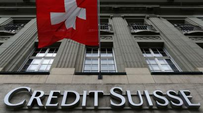 he logo of Swiss bank Credit Suisse is seen below the Swiss flag at a building in the Federal Square in Bern