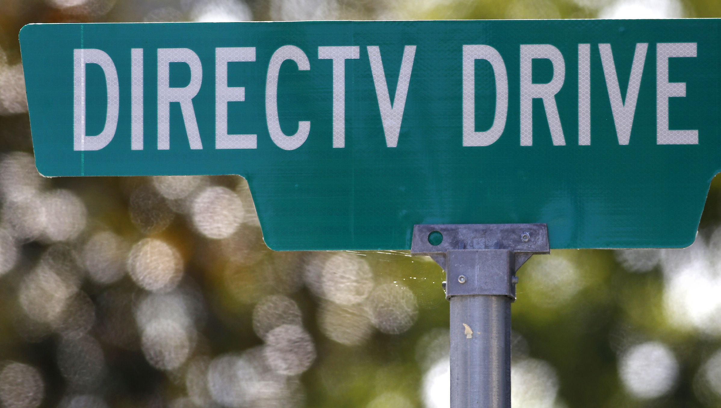A street sign at the headquarters building of U.S. satellite TV operator DirecTV is seen in Los Angeles, California May 18, 2014. AT&T's expected acquisition of DirecTV could provide the company with a pathway to expand its services into Latin America, where the satellite operator has 18 million subscribers and a higher growth rate than in the United States.  REUTERS/Jonathan Alcorn  (UNITED STATES - Tags: BUSINESS TELECOMS) - RTR3PQ2Z