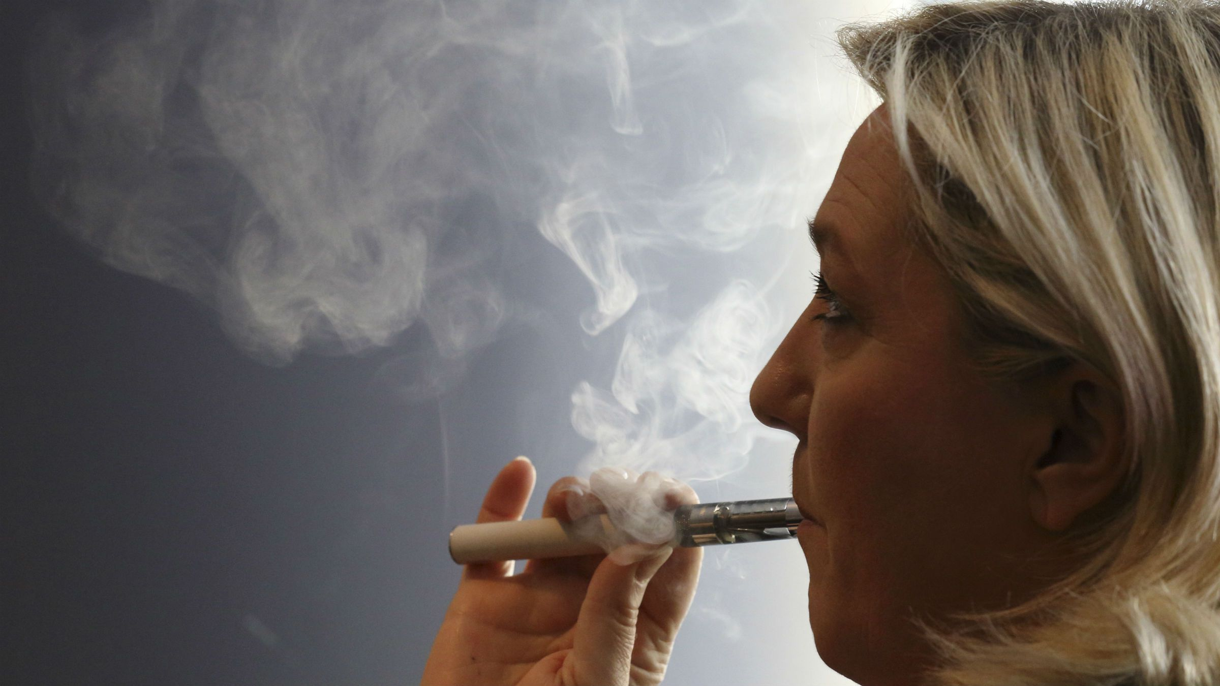 Marine Le Pen, France's far-right National Front political party leader, smokes an electronic cigarette as she attends a debate for the upcoming European Parliamentary elections organized by France 3 television in Lille, May 20, 2014.