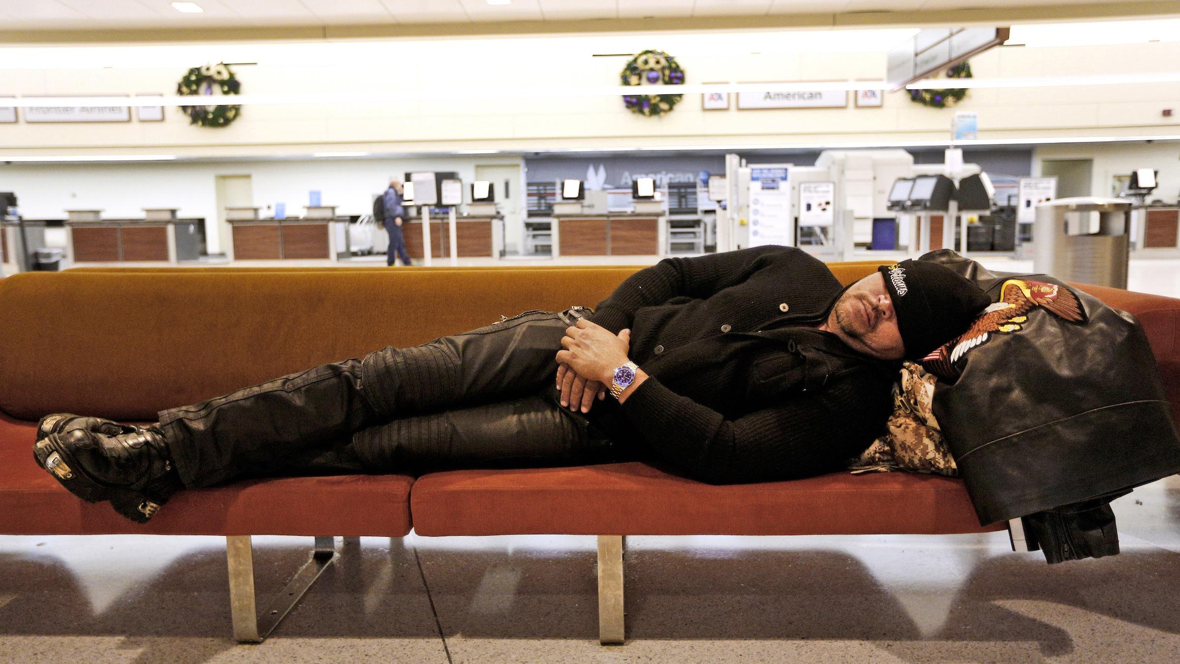 guy sleeping in airport