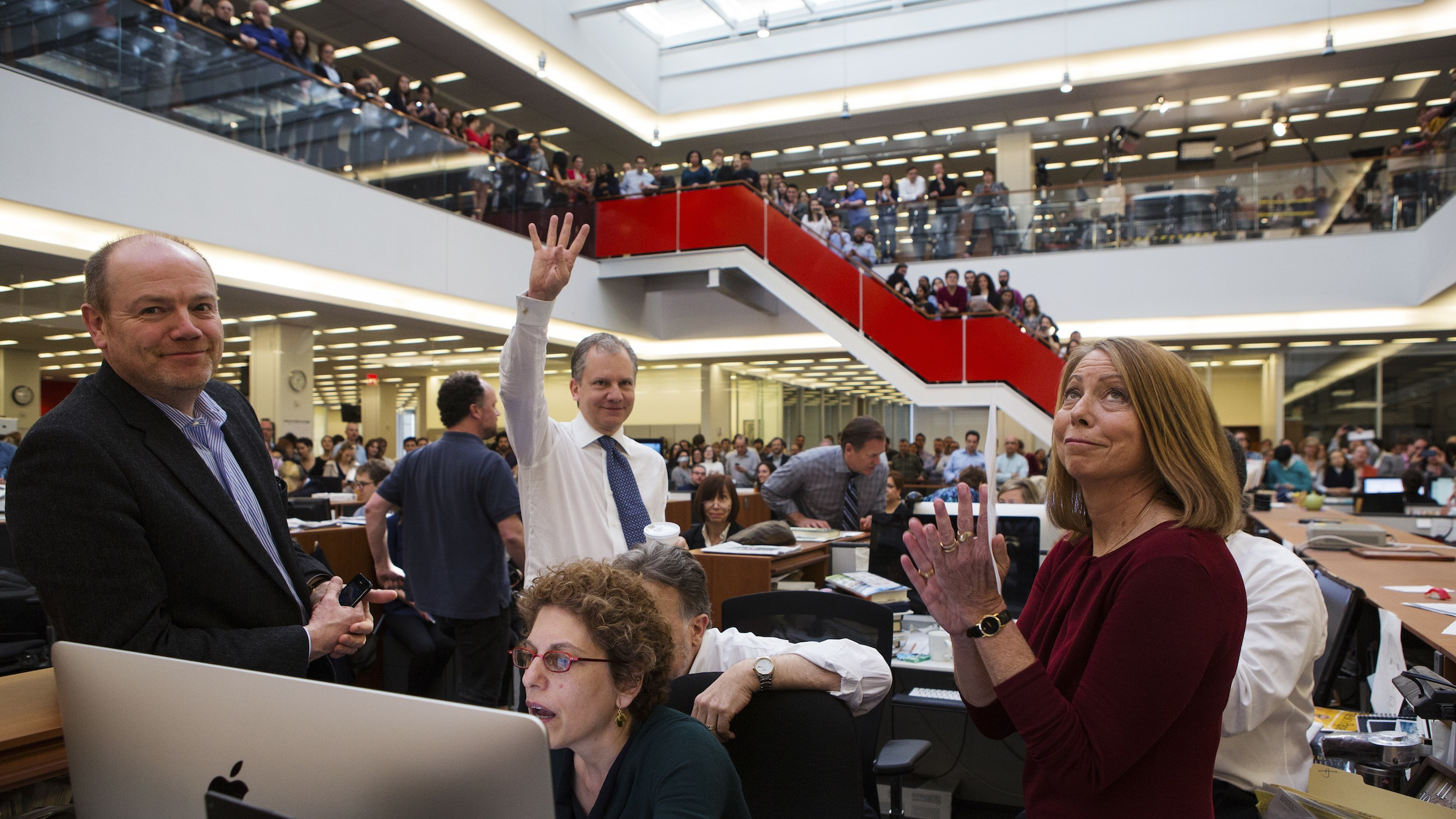 Publisher Arthur Sulzberger Jr. holds up four fingers to indicate the four Pulitzer Prizes won by the New York Times, as winners for the 2013 Pulitzer Prize are announced at The New York Times newsroom in New York April 15, 2013. Also pictured are (from L-R): CEO Mark Thompson, Sulzberger, Assistant Managing Editor Susan Chira, Editorial Page Editor Andrew Rosenthal (obscured by Chira) and Executive Editor Jill Abramson. REUTERS/Ruth Fremson/Pool (UNITED STATES - Tags: MEDIA SOCIETY) - RTXYN1U