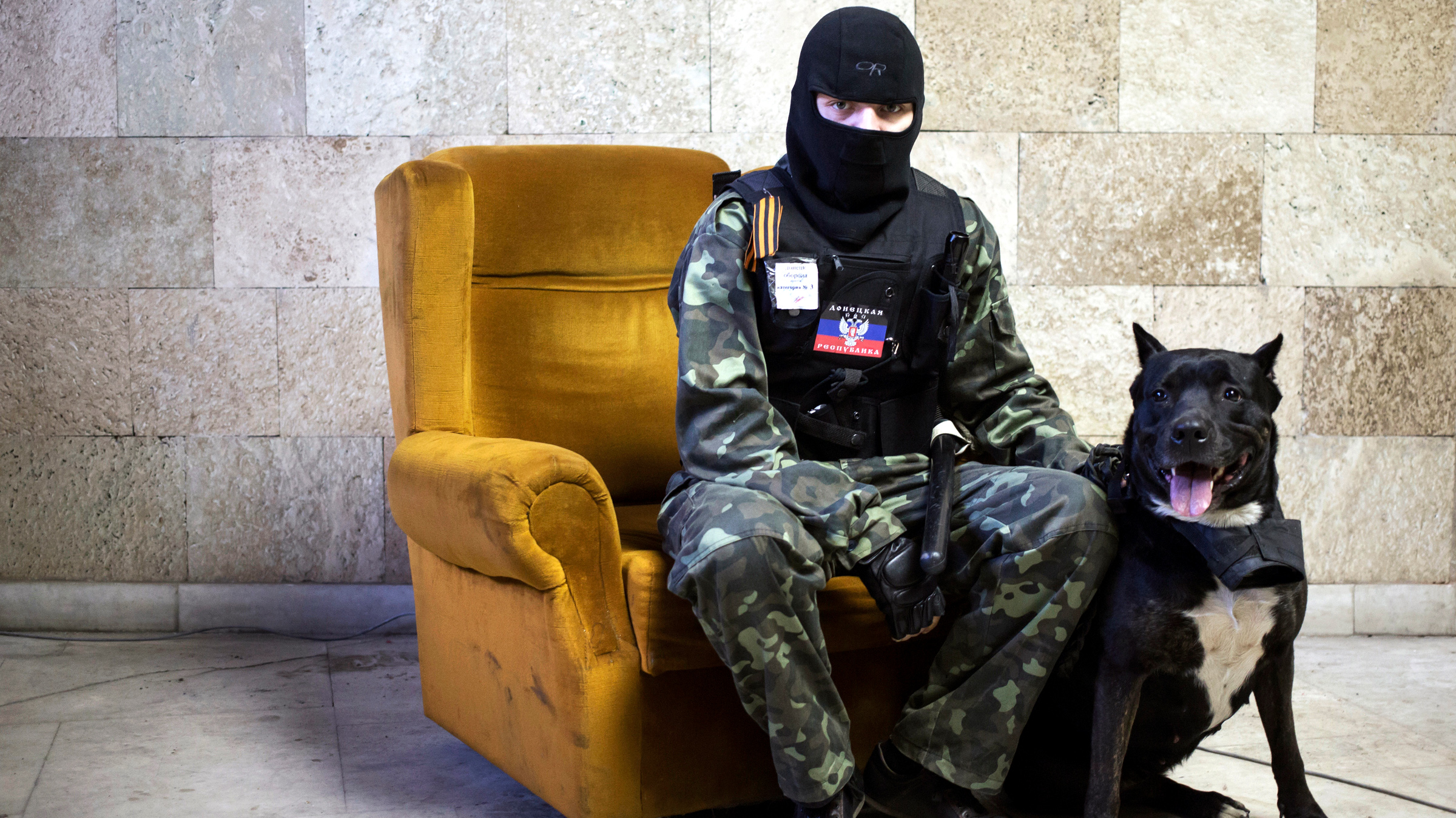 A masked pro-Russian protester sits beside a dog as he poses for a picture inside a regional government building in Donetsk, eastern Ukraine April 25, 2014. Picture taken April 25, 2014.