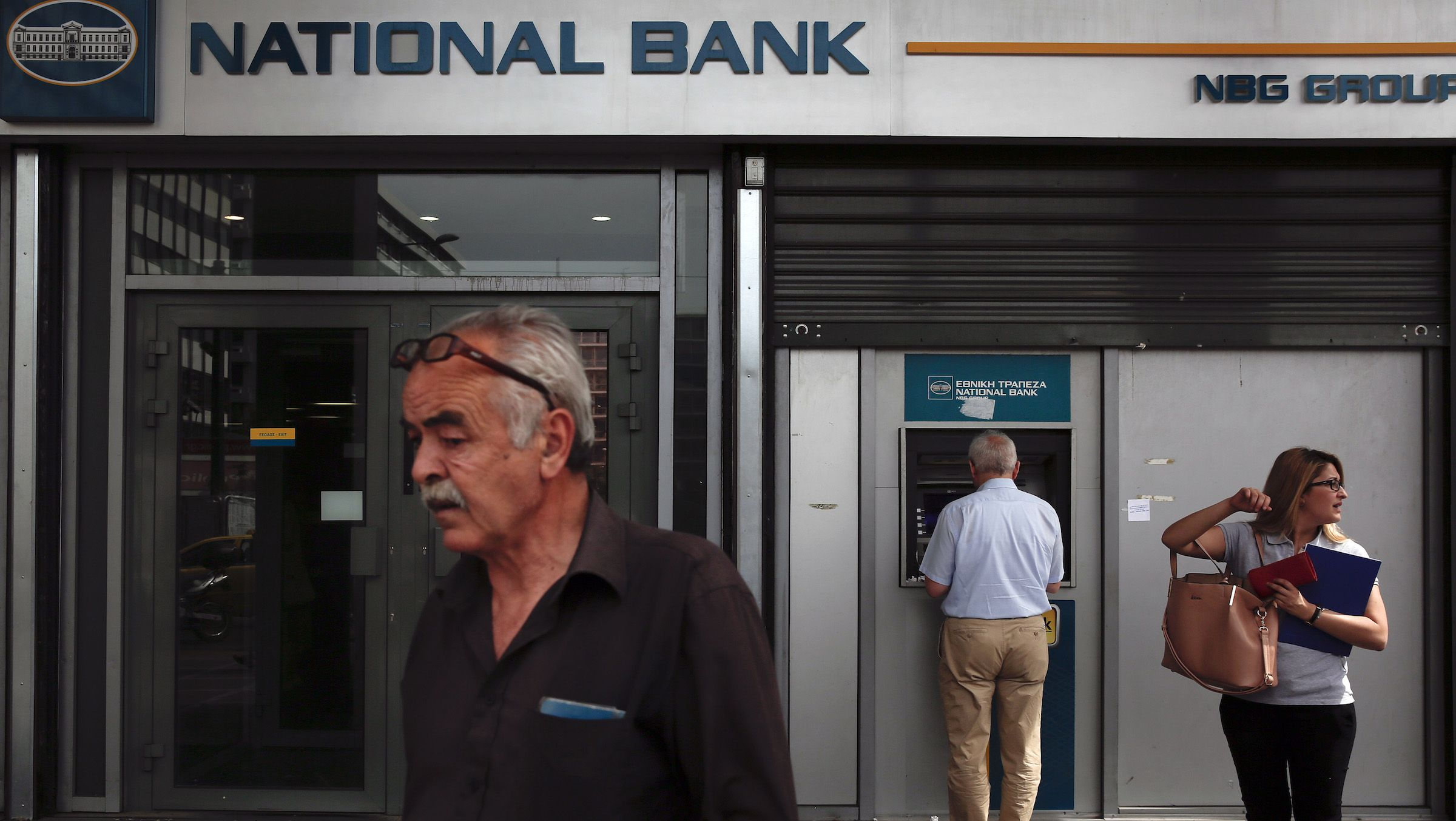 People are seen outside a National Bank branch in Athens