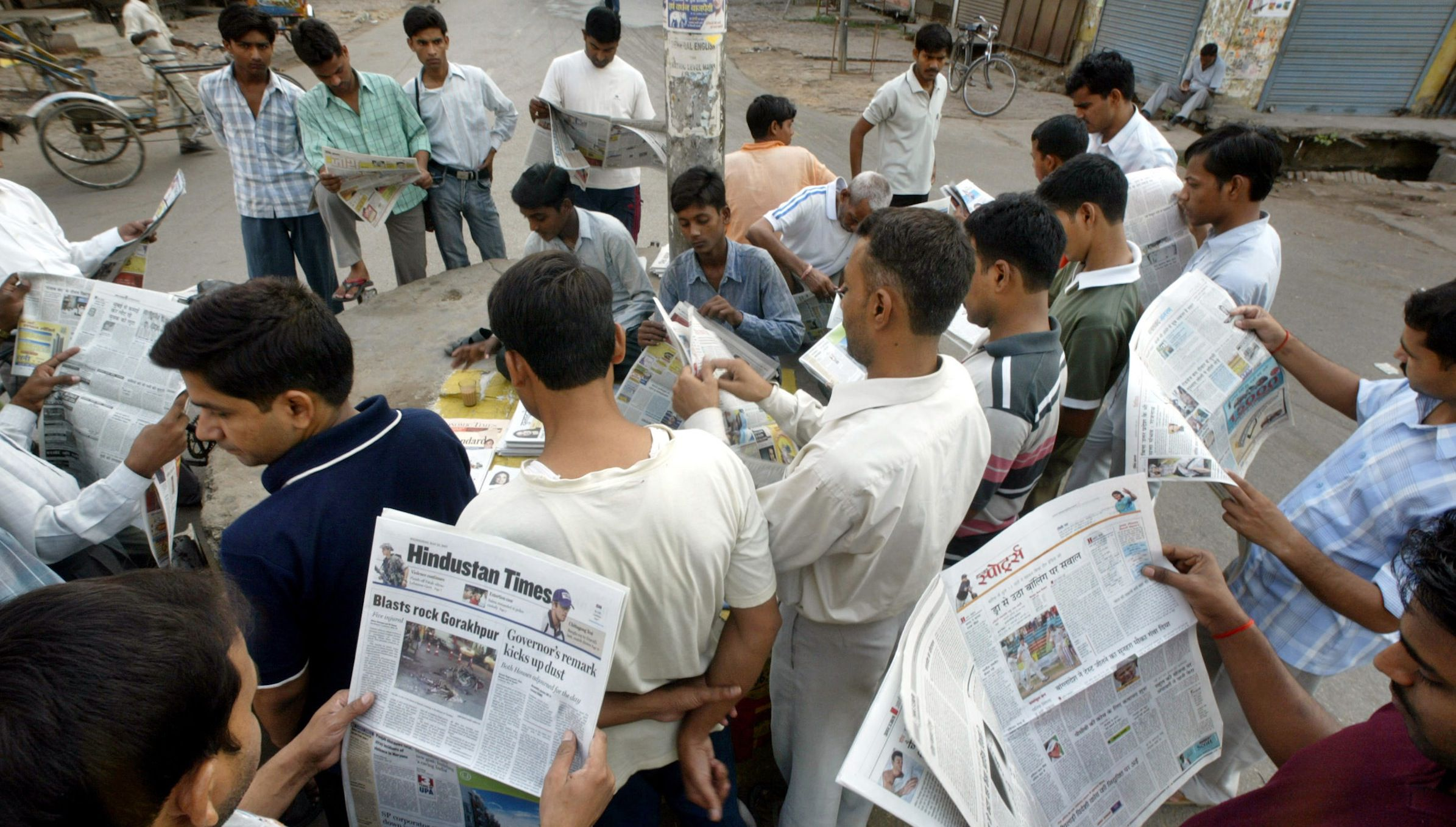 Allahabad University students read newspapers early morning around a newspaper vendor on a roadside, in the northern Indian city of Allahabad, Wednesday, May 23, 2007. Obituaries for newspapers are already being written in the United States but more than 150 million people read a newspaper every day in India, compared to 97 million Americans, and circulation numbers are soaring, and advertising is expected to grow by 15 percent this year. Roughly 11 million English newspapers are sold every day, while nearly 34 million Hindi papers are sold, according to India's Registrar of Newspapers. (AP Photo/Rajesh Kumar Singh)